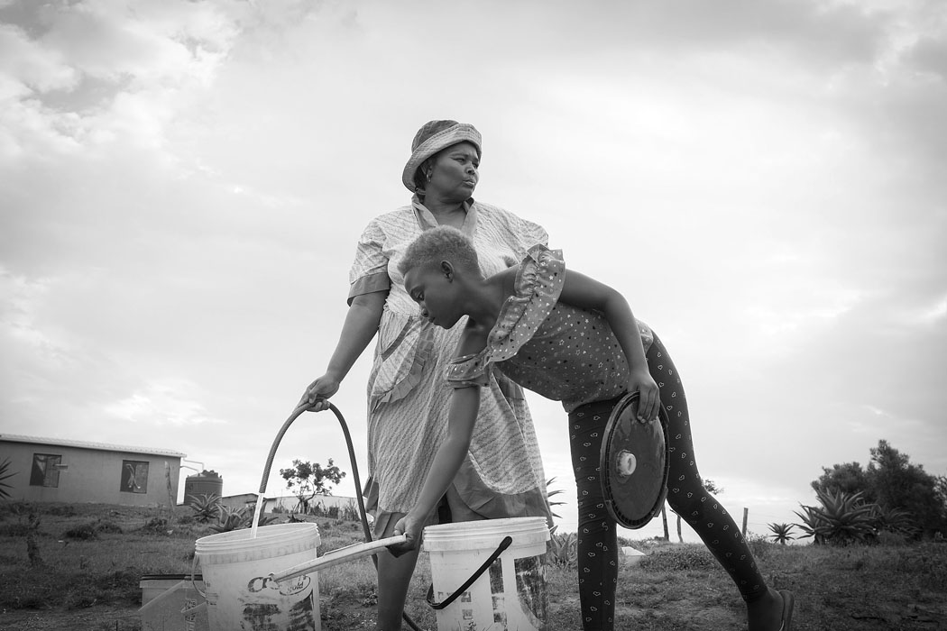 Bongeka Ngcobo,   Burden, 2018  Giclée Watercolour Paper  42 x 29,7 cm  Edition: 10  Bongeka Ngcobo - Extraordinary    Women and children usually bear the burden of having to collect safe and clean water for household uses in rural areas. Often this keeps them from attending school or a formal job. In this body of work, I am showing thoughts, feelings and emotions of what women and children have to go through to try better their lives in rural areas. I am identifying their strong hidden qualities, to better understand their reality and to express the interpretation of their world.    The idea of expressing in images the everyday life of women and children at the Ndondwane Village, KwaZulu Natal came about in March 2015, when I saw a demand and need for their story to be told. Through my work I hope to make their issues apparent in an attempt to try and bring about change in the community towards a future where they can easily get access to clean water and safe electricity.