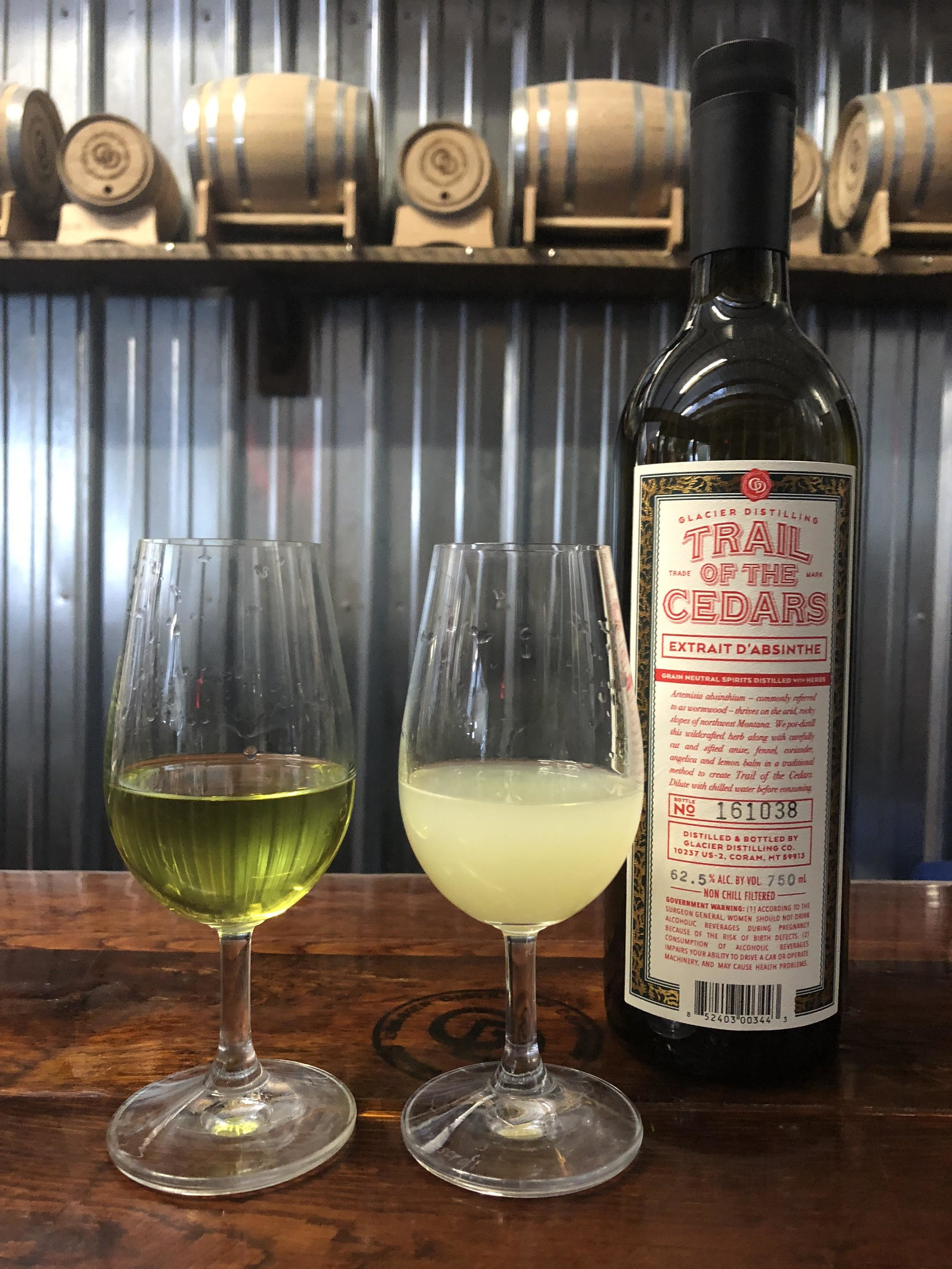 """The glass on the left displays the natural green coloring of a new batch of Trail of the Cedars Absinthe, while the glass on the right shows the spirit's coloring after the physical reaction caused by """"La Louche."""""""