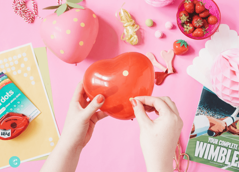 How to make a super cute strawberry balloon garland using heart shaped balloons from Hello Party