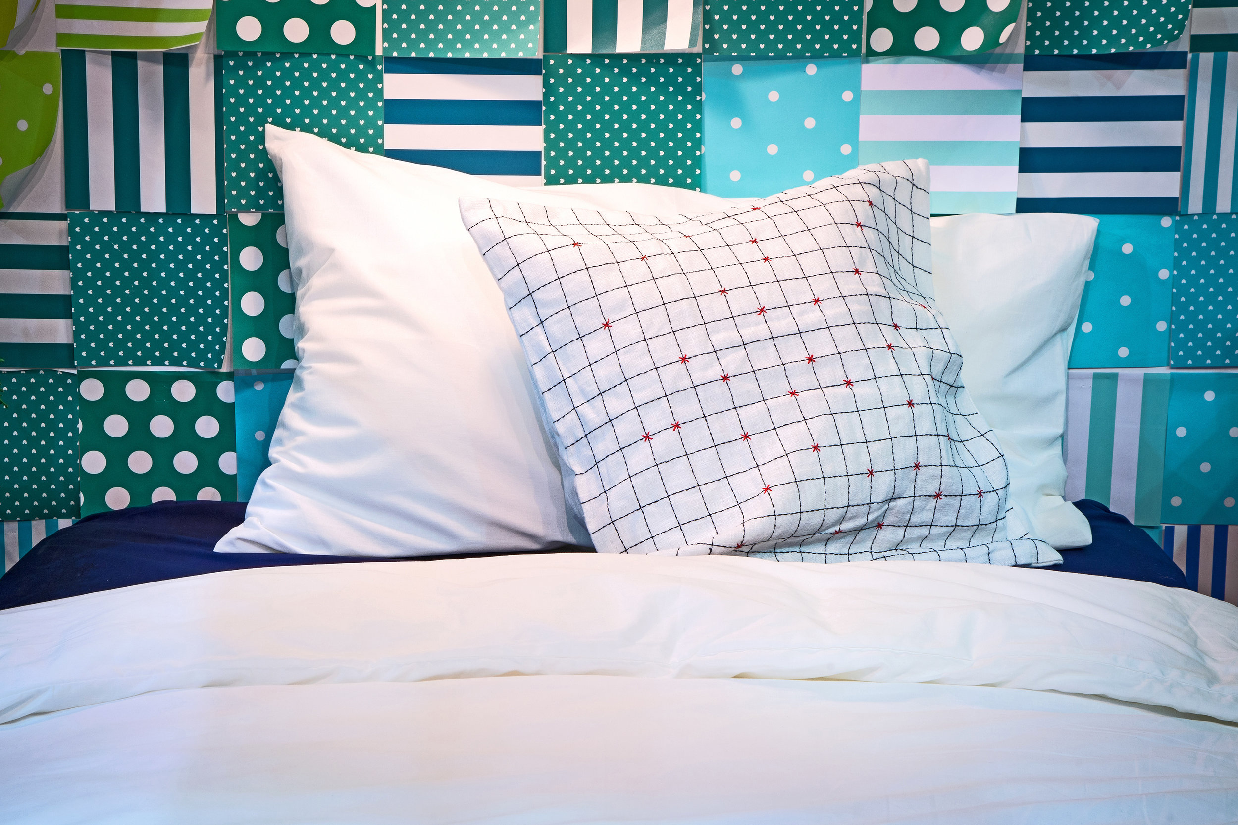 Colorful Custom Designed Headboard  Polka dot and striped fabrics of navy, teal and aquamarine create colorful patchwork headboard for coastal bedroom  Design Thought:  Purchase a used or inexpensive headboard, preferably a rectangle.  Mix and match approximately six fabrics in three colors each of polka dots and stripes.  Design a pattern similar to patch quilt blocks and have headboard upholstered.  Remember, the plusher the batting underneath the fabric, the more cushioned the headboard.