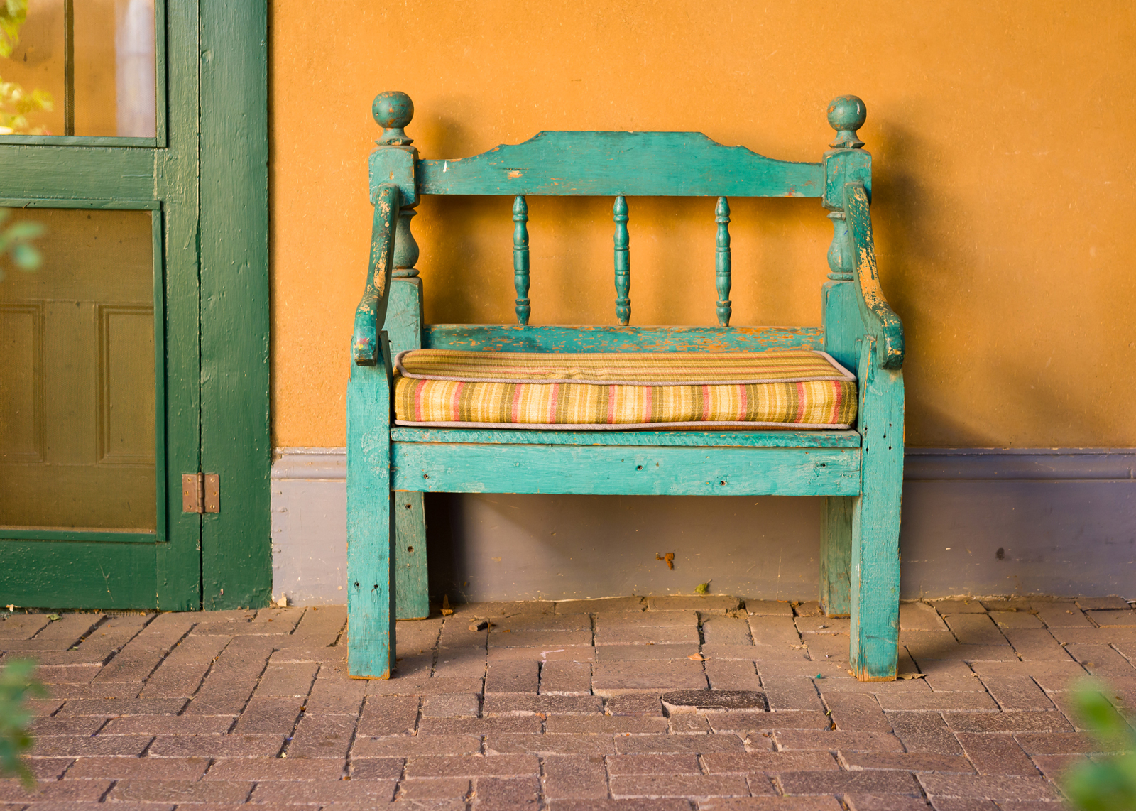 "An old bench on porch  Design Thought:  Bring that teal bench that you love so much inside to the mudroom or hallway of your beach house.  Reupholster the seat cushion with a new teal patterned fabric, accented with the same tangerine color that is on the porch wall.  To highlight your coastal piece, select a color from the chart below, such as taupe or brown, to paint an interior accent wall where the bench will be placed.   It becomes ""pIcture perfect"" just like the sand greeting the ocean."
