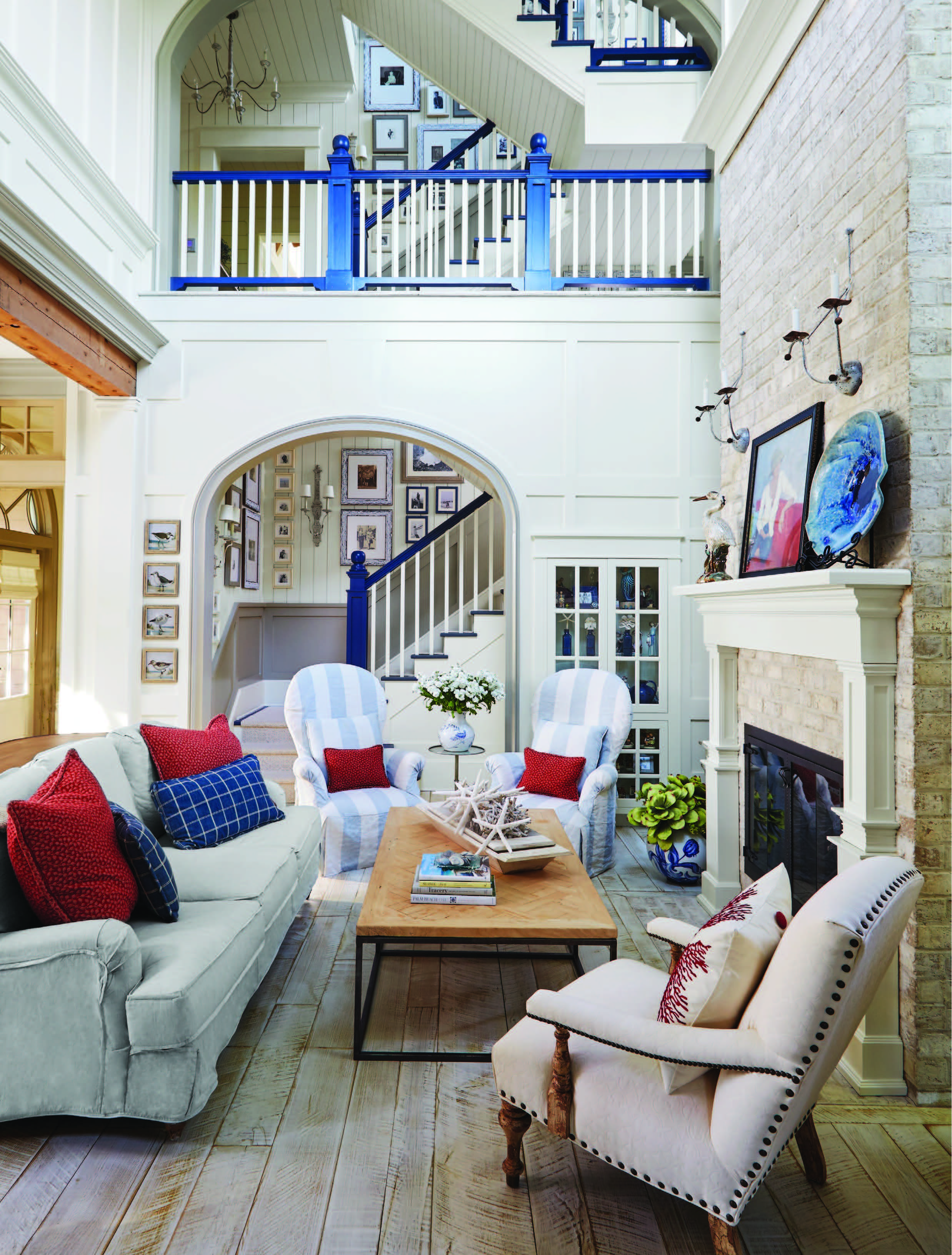 Susan painted the stairway railings and risers a bright blue to create a dramatic focal point in the living room. The exposed brick fireplace, rough-hewn beams, and whitewashed oak floors provide a texture-rich yet neutral foundation that allows colorful accents to pop.