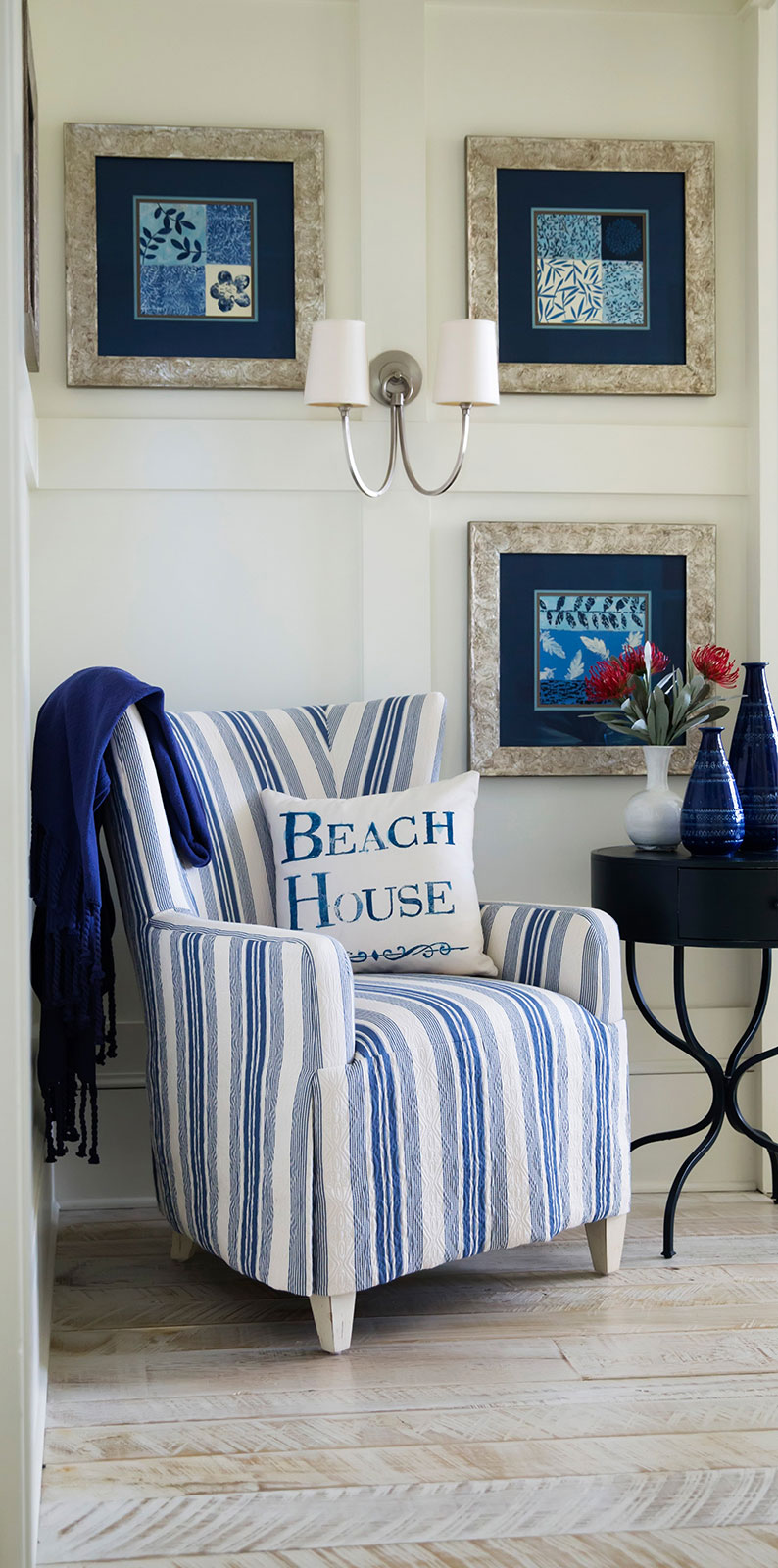 At The Beach: Inviting entry to guest bedroom  Resources: Chair: Century Furniture   Fabric: CR LainePattern: Marley Indigo  Throw: Pottery Barn   Side Table: Pottery Barn  Wall Sconce: Visual Comfort   Vases: Ethan Allen  Art Prints: Art.com;   Framing: Michaels  Design Thought: It is convenient to have a chair or bench to sit on in the bedroom. A chair provides a place to rest at the beginning or end of the day. Adding a small table and reading light offers a cozy spot to unwind or just take it easy for a few minutes.