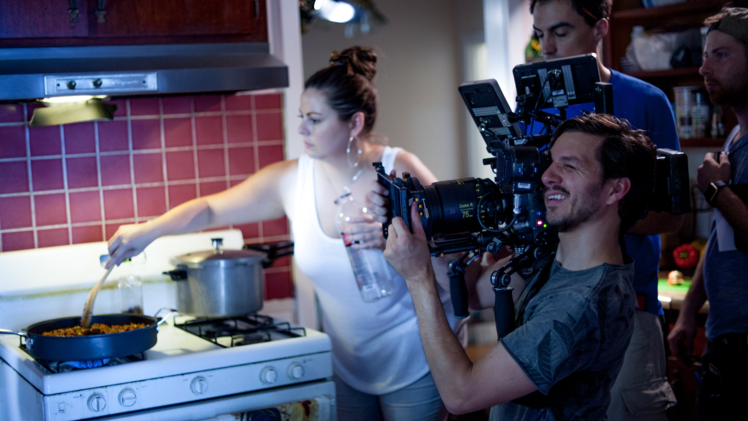 Director Claudia Murray stirs a skillet of picadillo while Director of Photography Ben Gaskell captures the scene.