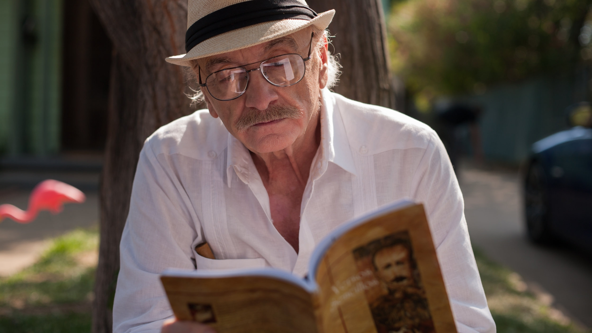 Abuelo (Ruben Rabasa) enjoys a book, cigar, and Cuban coffee while waiting for Vanessa to arrive.