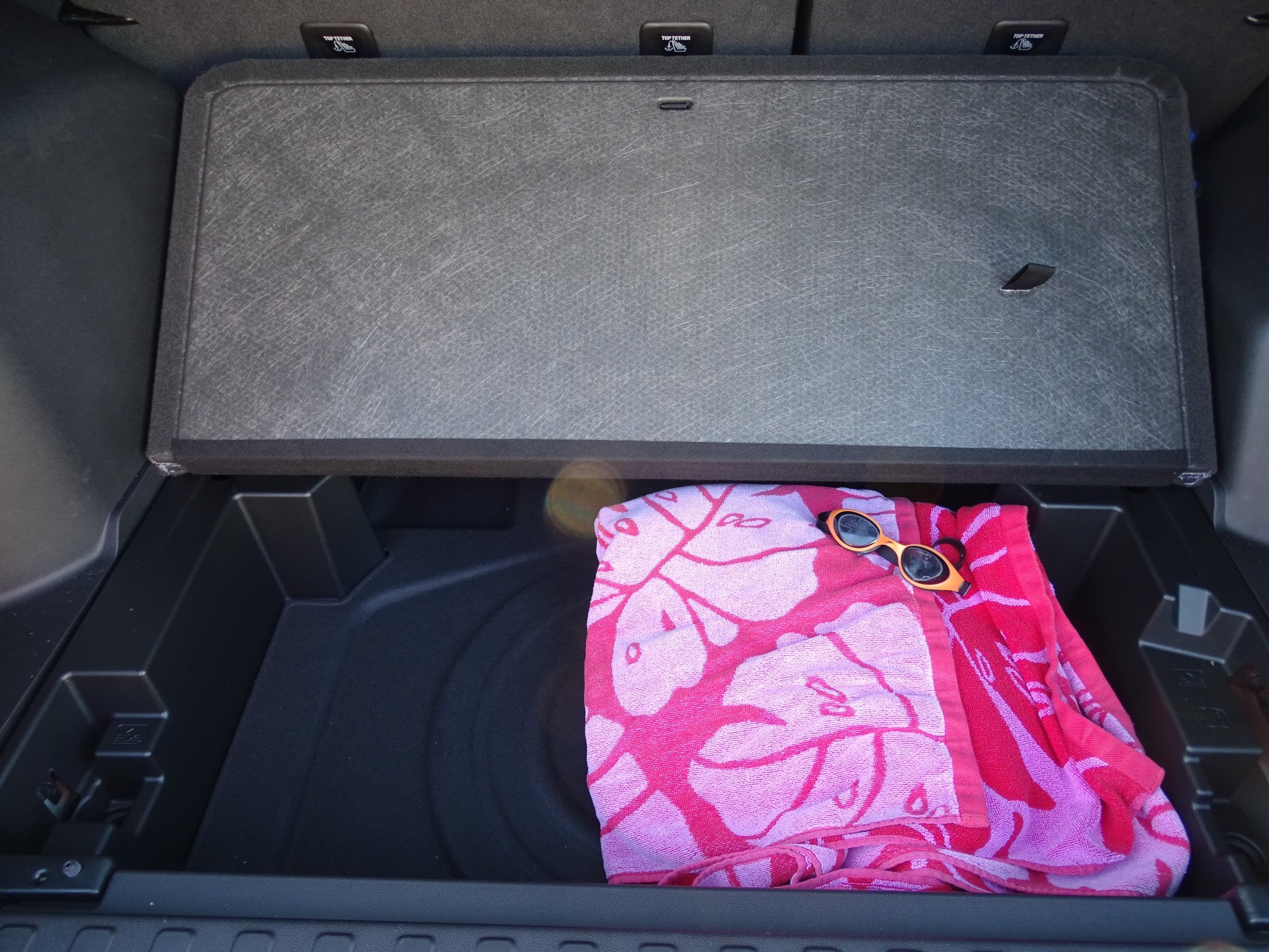 Secret storage compartment in the trunk, currently holding pool supplies, will be put to good use on future road trips.