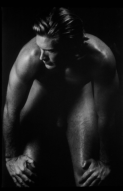 "Dianora Niccolini - Most of the photographers here identify (or can historically be identified) as queer or gay men. Dianora Niccolini, on the other hand, offers a fascinating view of men as softly erotic in a way that (sometimes literally) places them as complementary to women. Her images linger on muscles and tend, like some of Mapplethorpe's, toward a more ""ideal"" vision of brawny muscularity while at the same time making those burly bodies vulnerable. Stockton Bending (1996) exemplifies this—and my love for the reduced backgrounds continues, along with high contrast (though note that this image tends more towards obscuring with its lighting)."