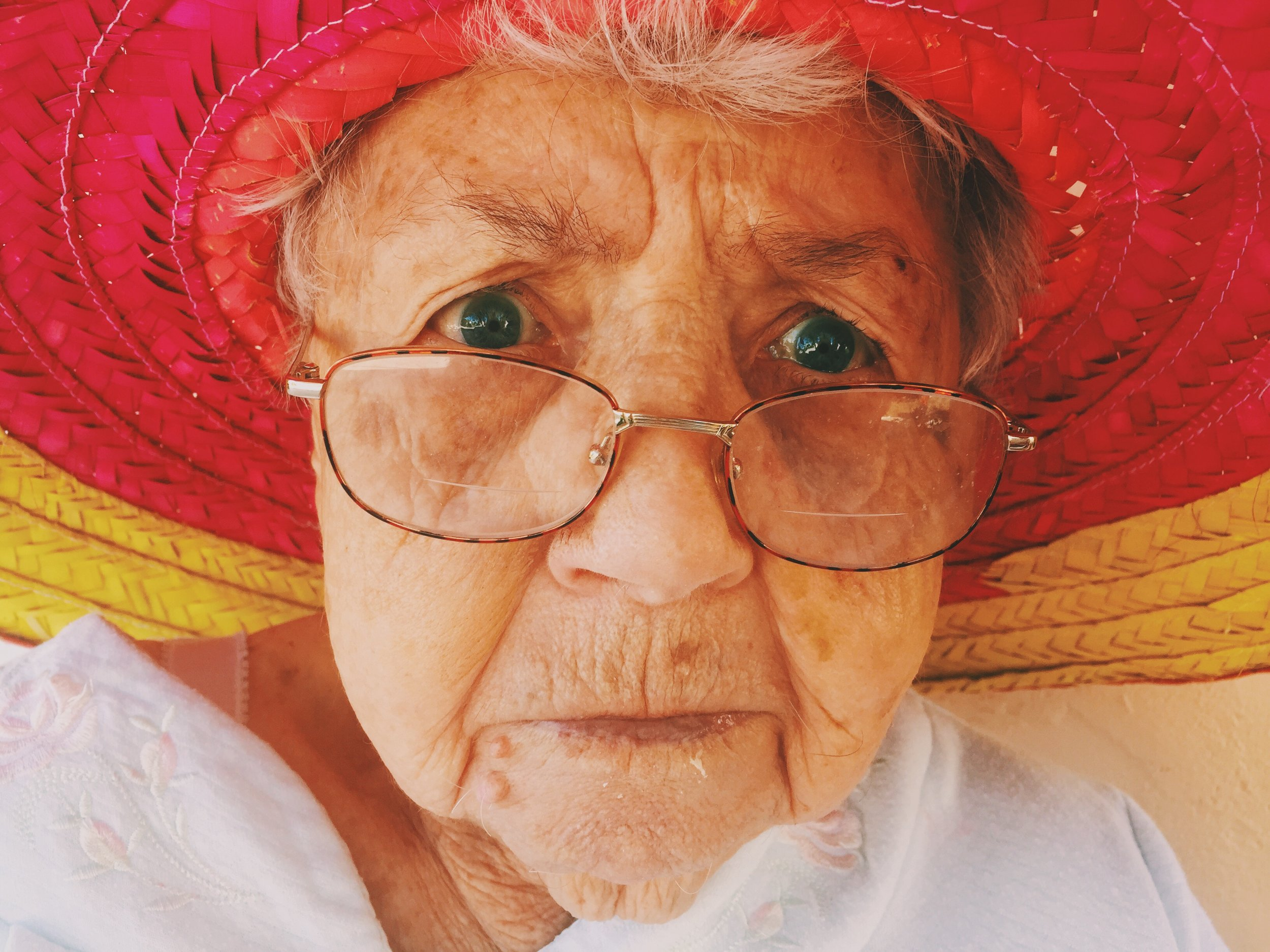 Grandma wearing glasses and hat scowling at camera. Photo by Unsplash