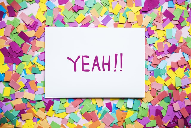 """Yeah!!"" written on a sign with confetti. Photo by Pexels"