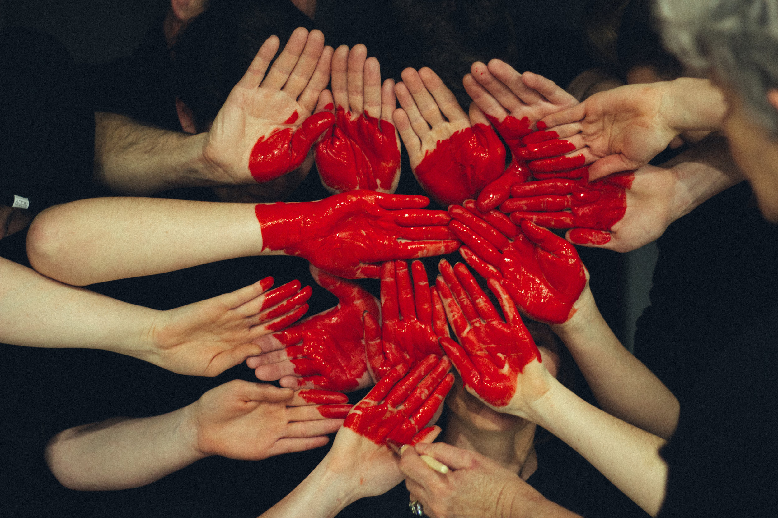 Hands grouped together with red paint to form a heart. Photo by Unsplash