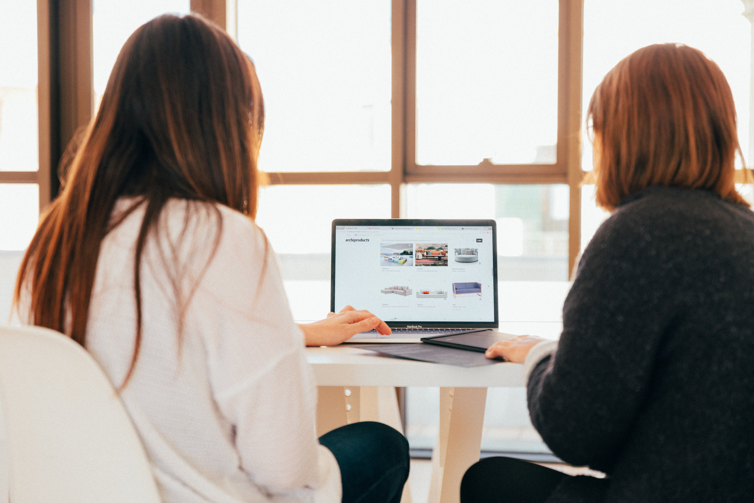Photo of two women sitting in front of a laptop by Unsplash.