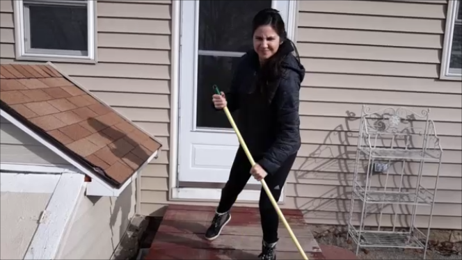 Photo of me sweeping the backstoop with wire shelving next to the back door in November 2018.