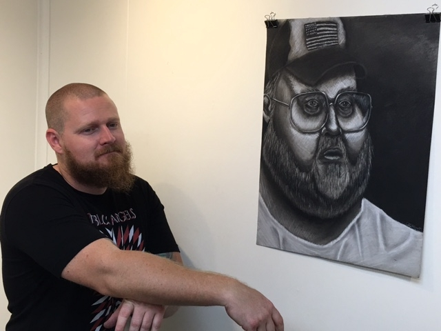 Cory Slawson, phICA's Logistics Manager, hanging a Christian Stewart drawing, 4-16-16