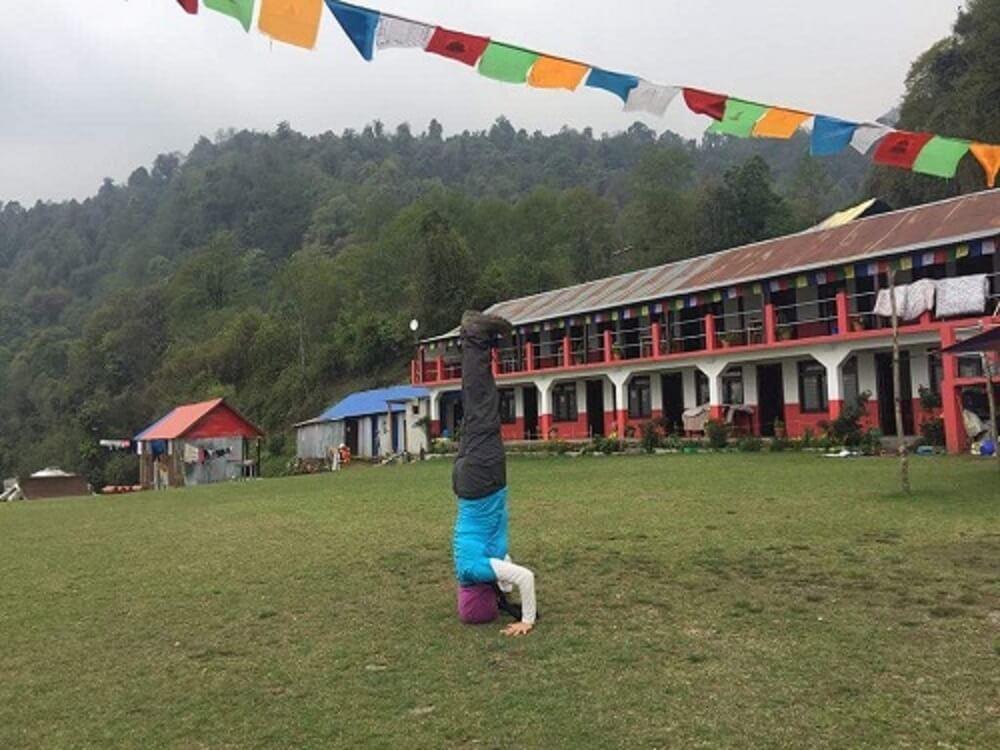 U70 lady posing perfect headstand yoga in Tadapani, Nepal