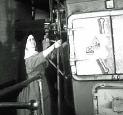 "Sr. Mary of the Visitation Cowles tends to the boiler in the ""dungeon."""