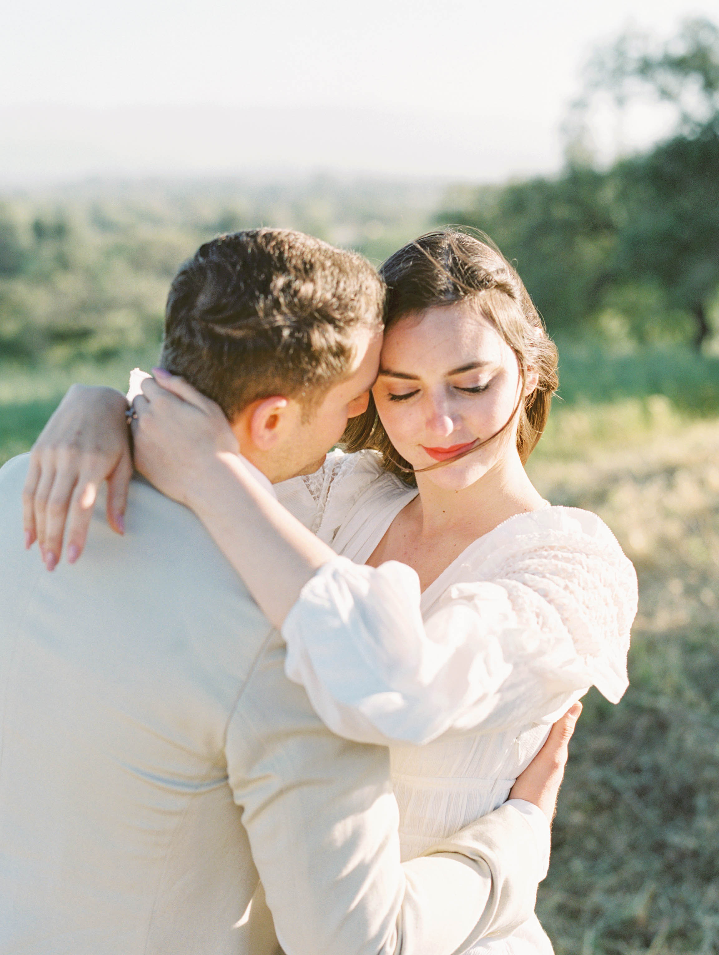 (C) Kelsey Cowley Photography. Kelsey is a published photographer based in California, photographing destination weddings, portraits, and editorials throughout the world. Boy is looking at girl, girl has her arms around boy, girl is looking down, couple is standing in a field in Santa Ynez.