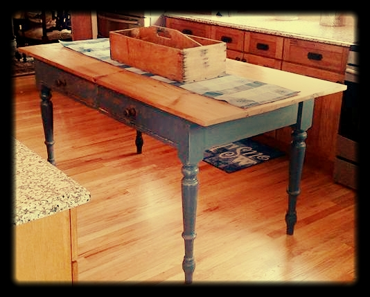 This kitchen Island was custom designed and built by Craig. Craig used an antique table based provided by the customer, used barn wood to build the counter top and added feet to increase the height. Feet were custom color matched.