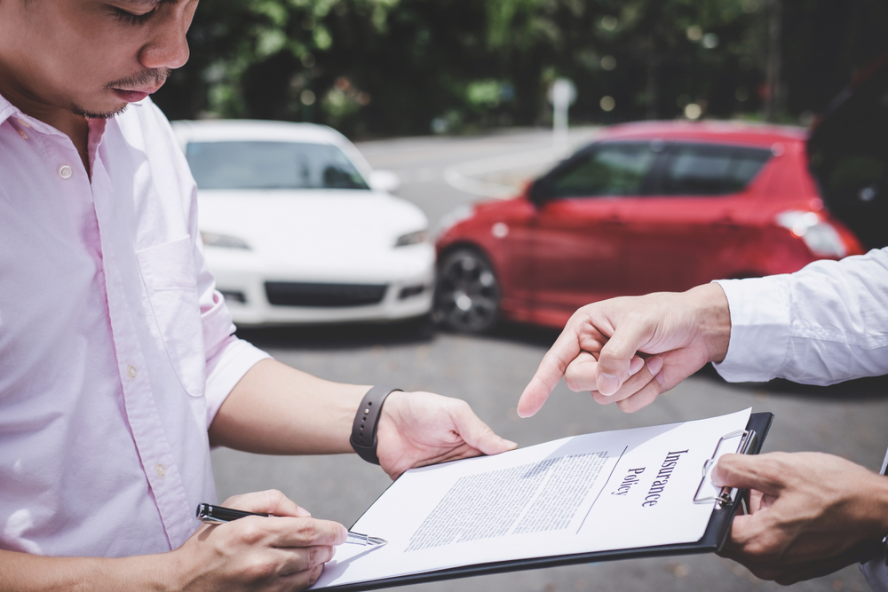 Car Insurance Agent examine Damaged Car and customer filing signature on Report Claim Form process after accident in OKC.jpg