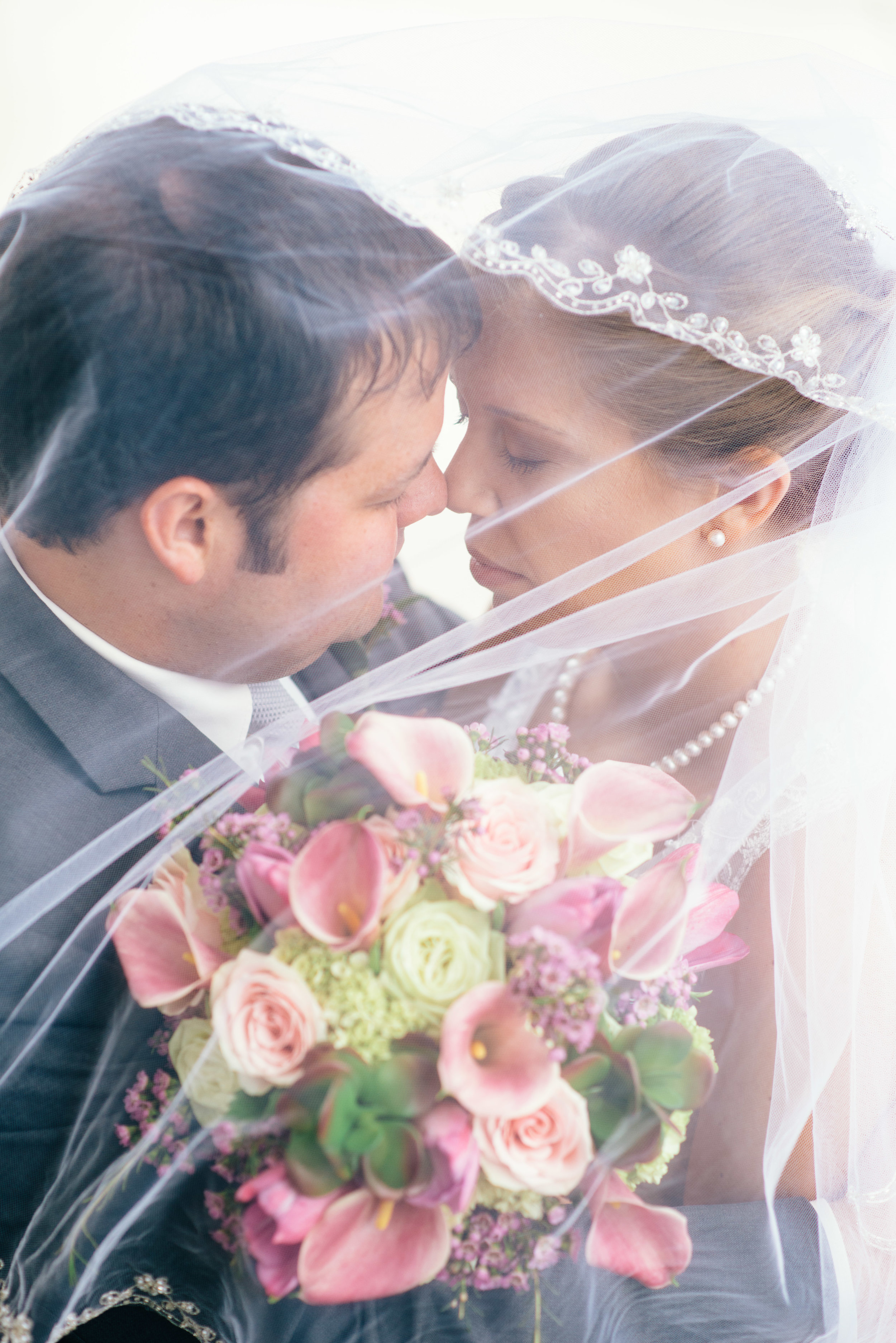 Bride wearing Tiffany's pearls and her groom sharing an intimate moment under a lace veil