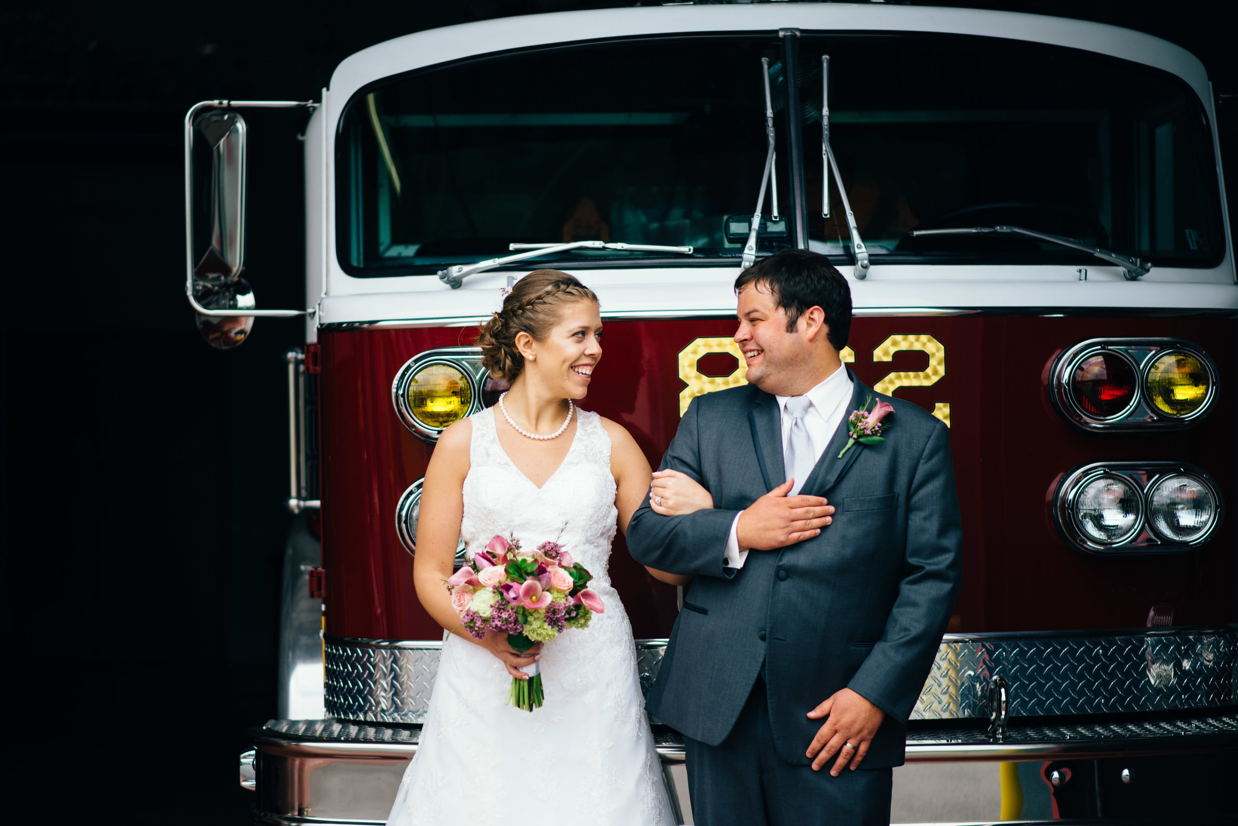 Bride and groom smiling at eachother in front of a vintage 1980's fire truck at the local Summerhill Volunteer Fire Company.