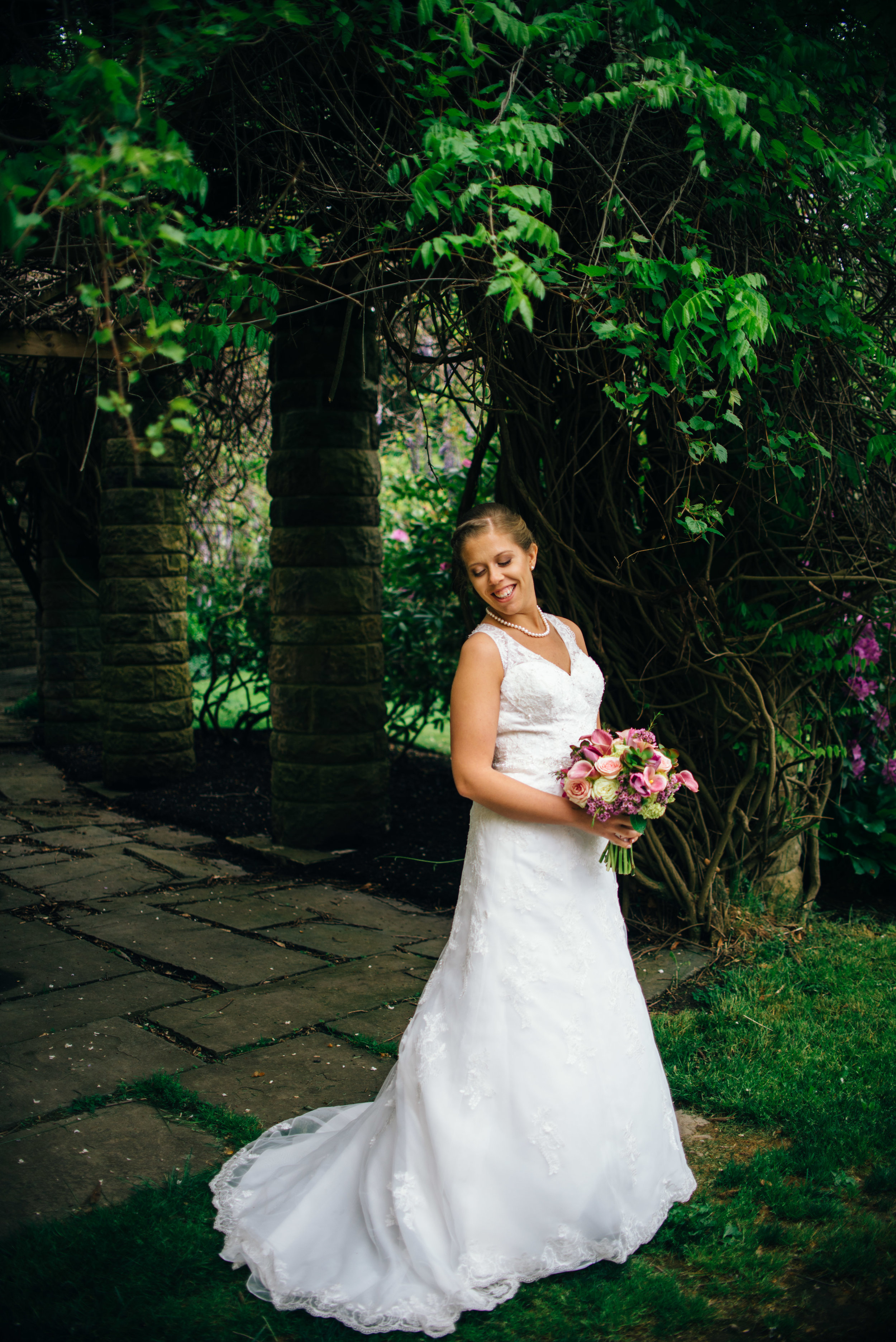 Bride standing in monastery garden in front of blooming arbor, looking over shoulder at her lace wedding gown train
