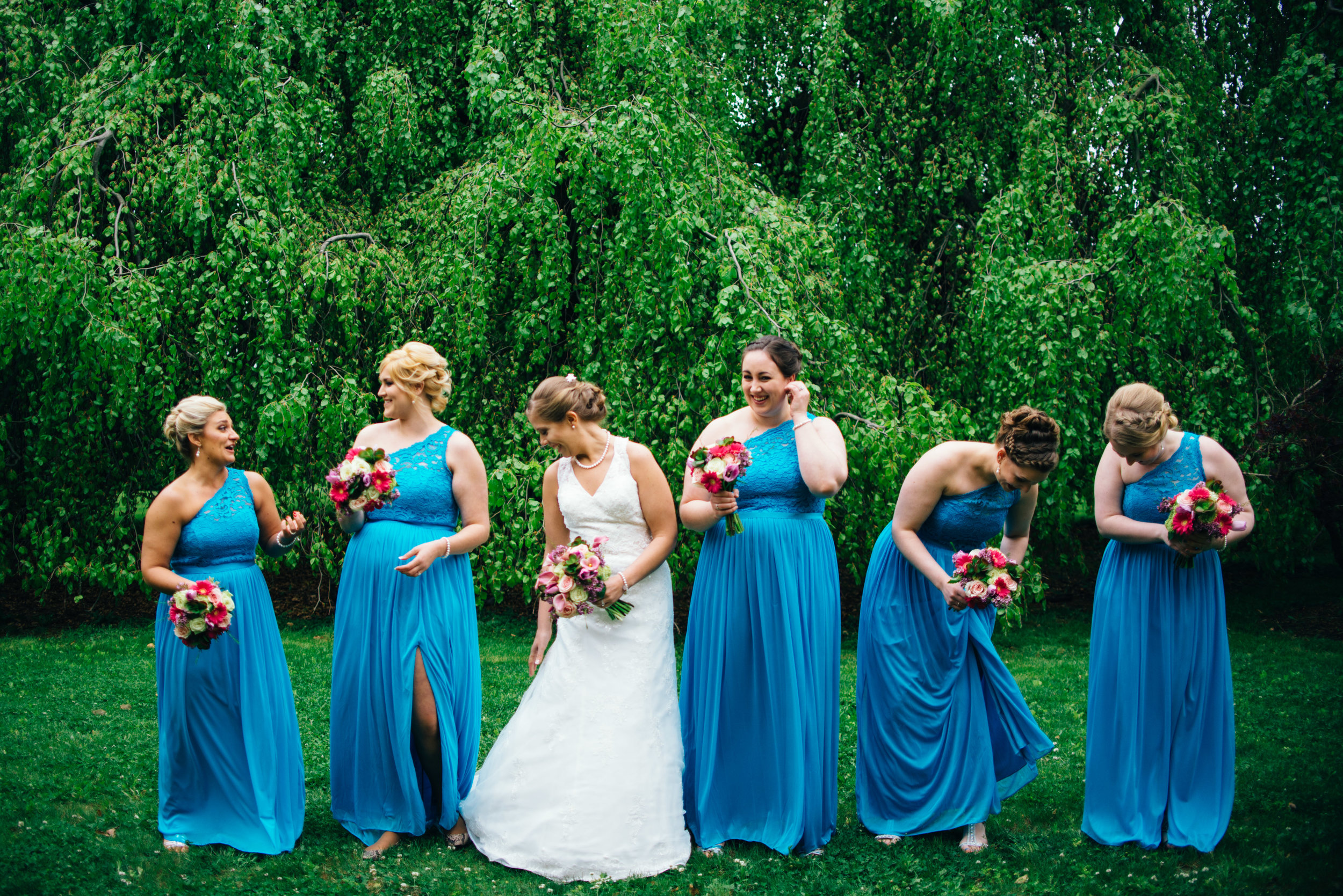 candid wedding photo of bridesmaids wearing blue one-shoulder dresses with pink bouquets