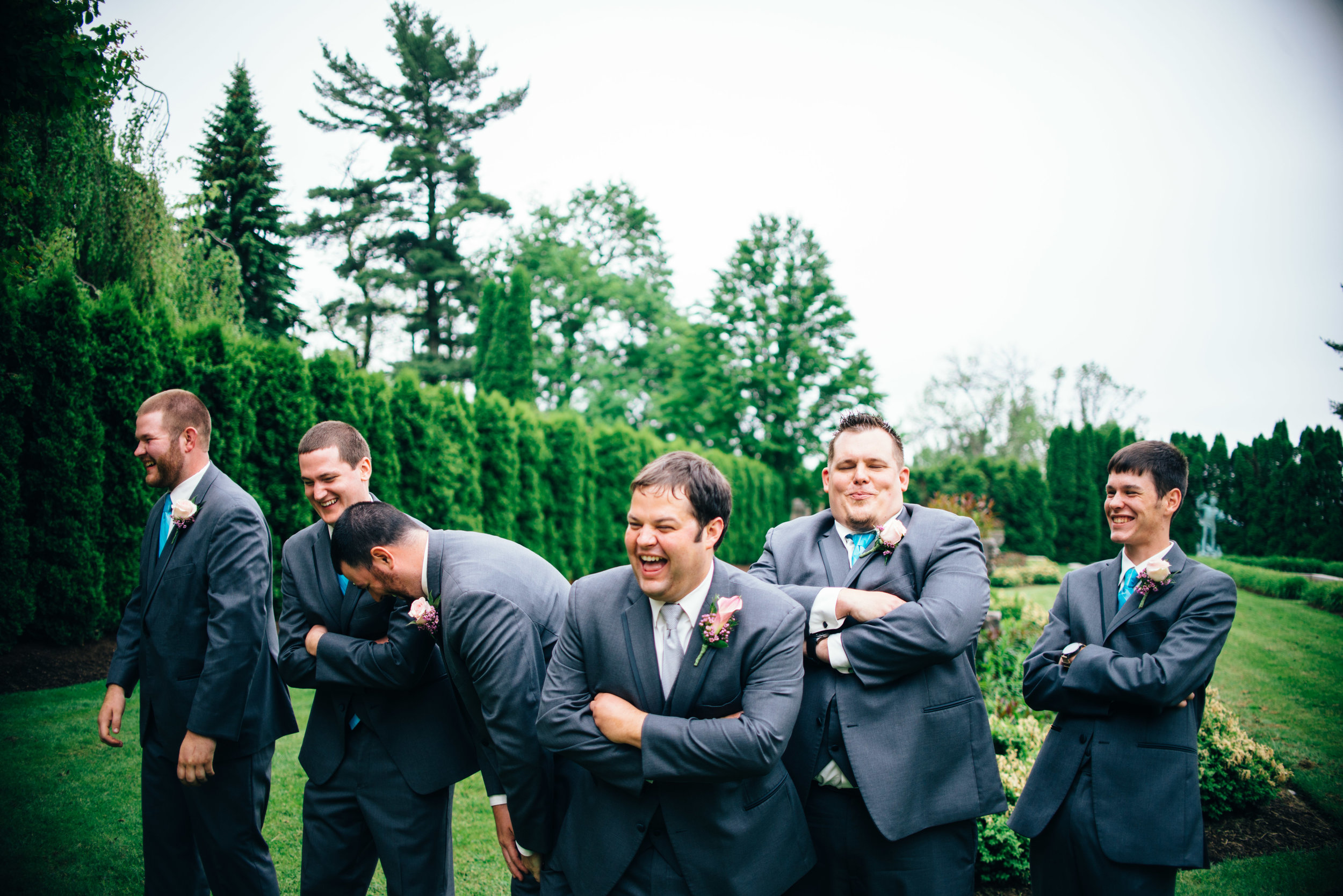 Candid photo of five groomsmen and a groom standing in a garden laughing