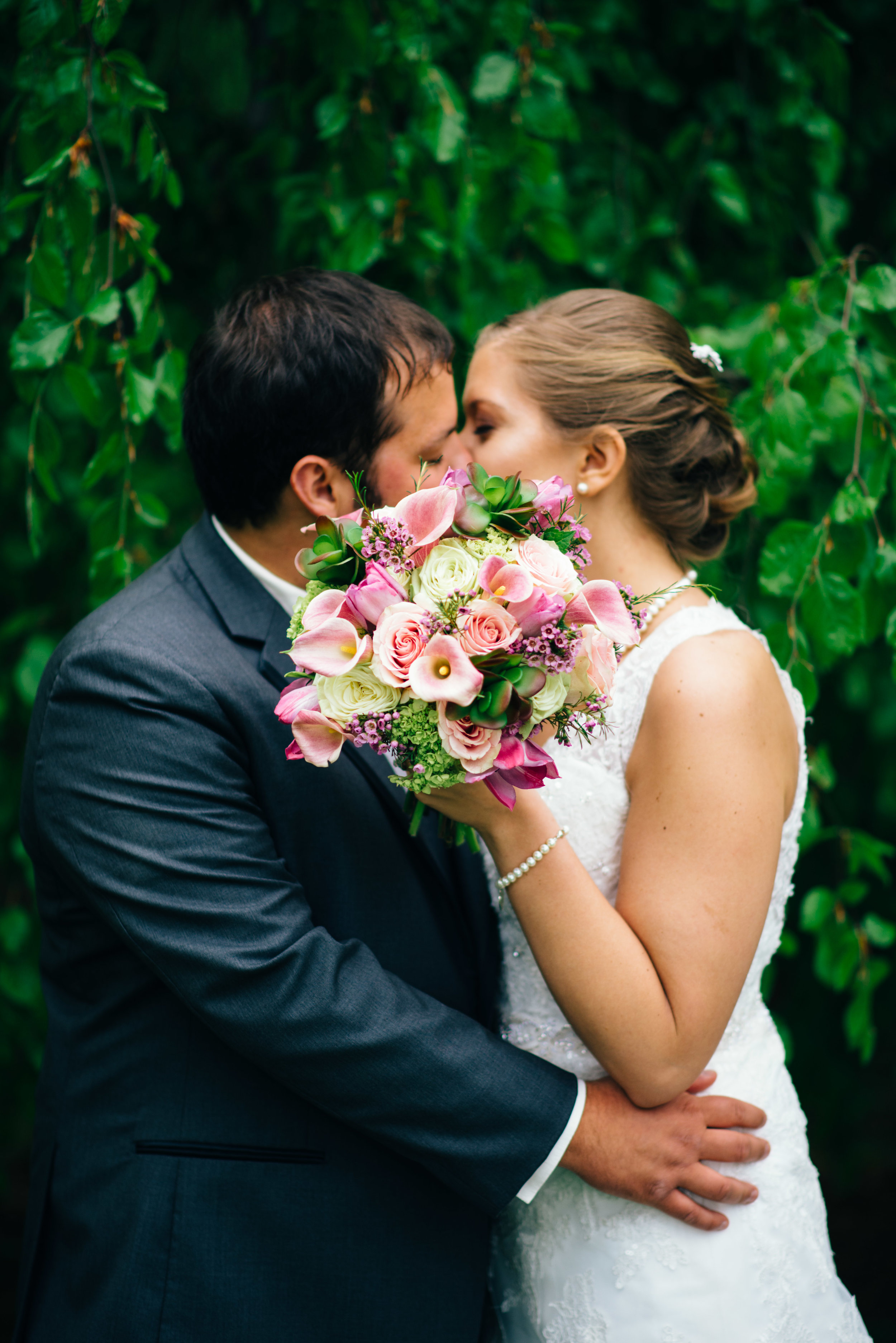 bride and groom kissing in front of a willow tree with pink and purple wedding bouquet covering faces