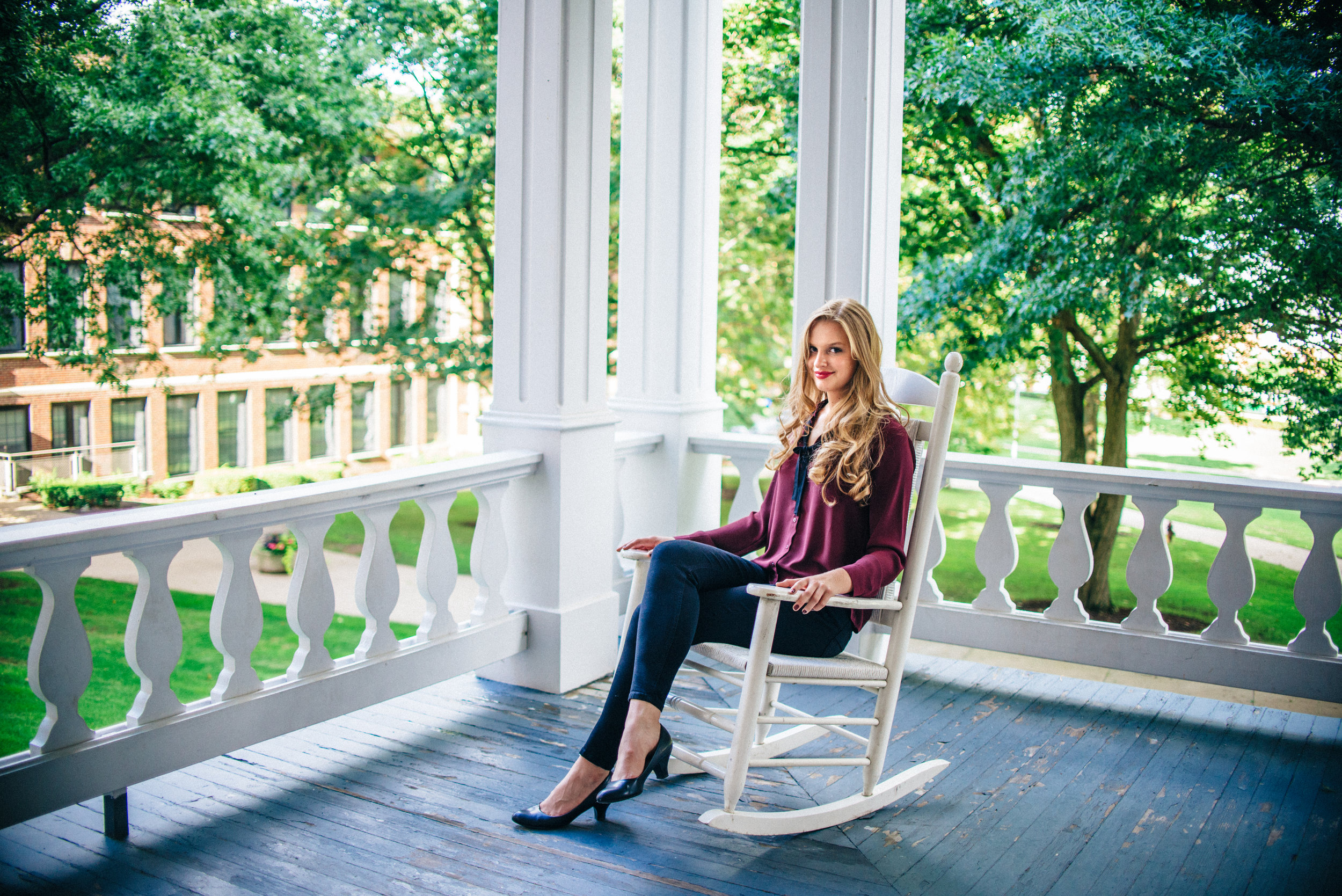 Blonde senior model in maroon blouse sitting on white rocking chair on the porch of Sutton Hall at Indiana University of Pennsylvania.
