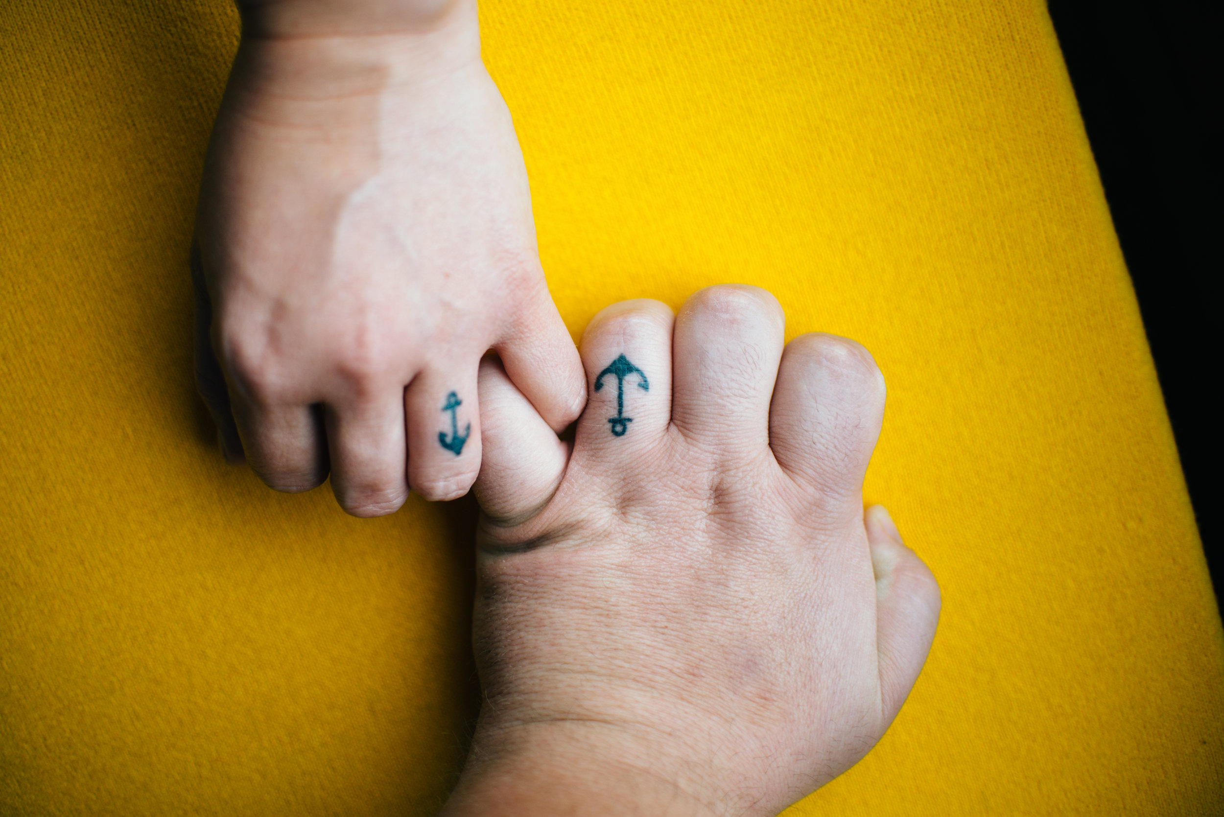 Hands in pinky promise against a yellow background with wedding ring tattoos of anchors on ring fingers