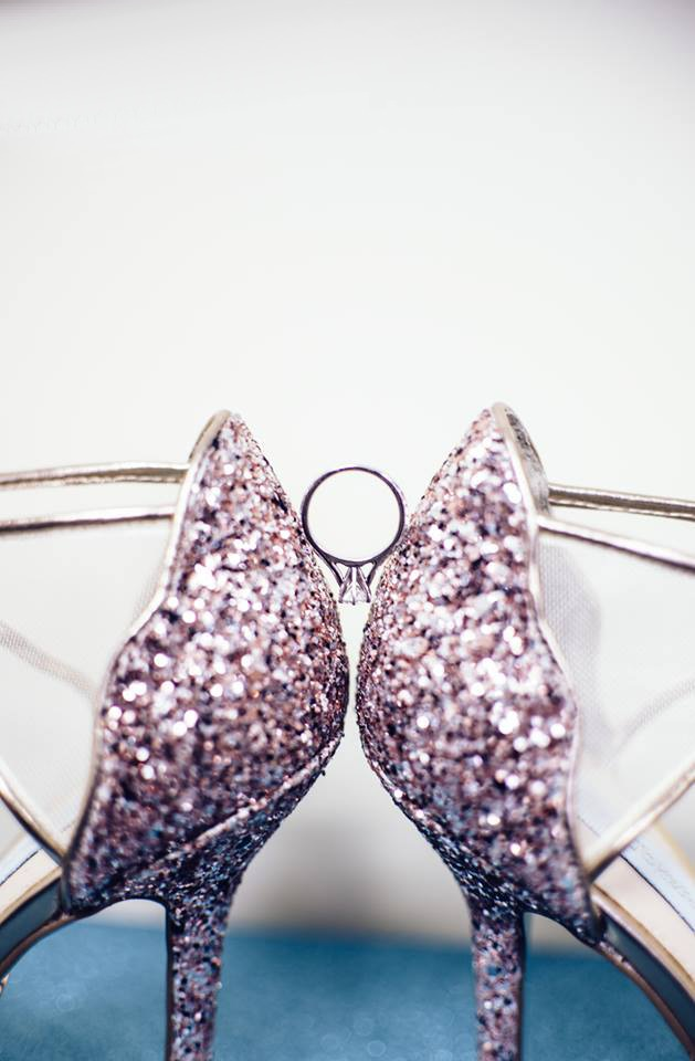 engagement ring balanced between pink sparkly high heels worn by a bride on her wedding day