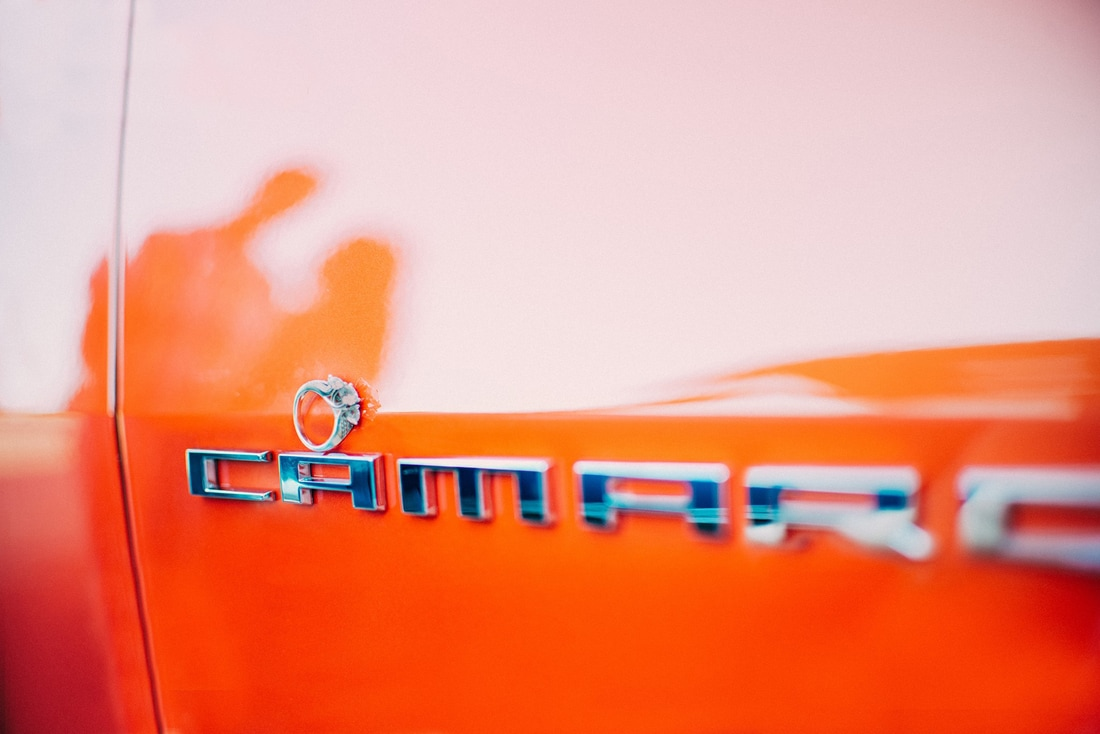 engagement ring with orange camaro and silhouette of couple in car paint
