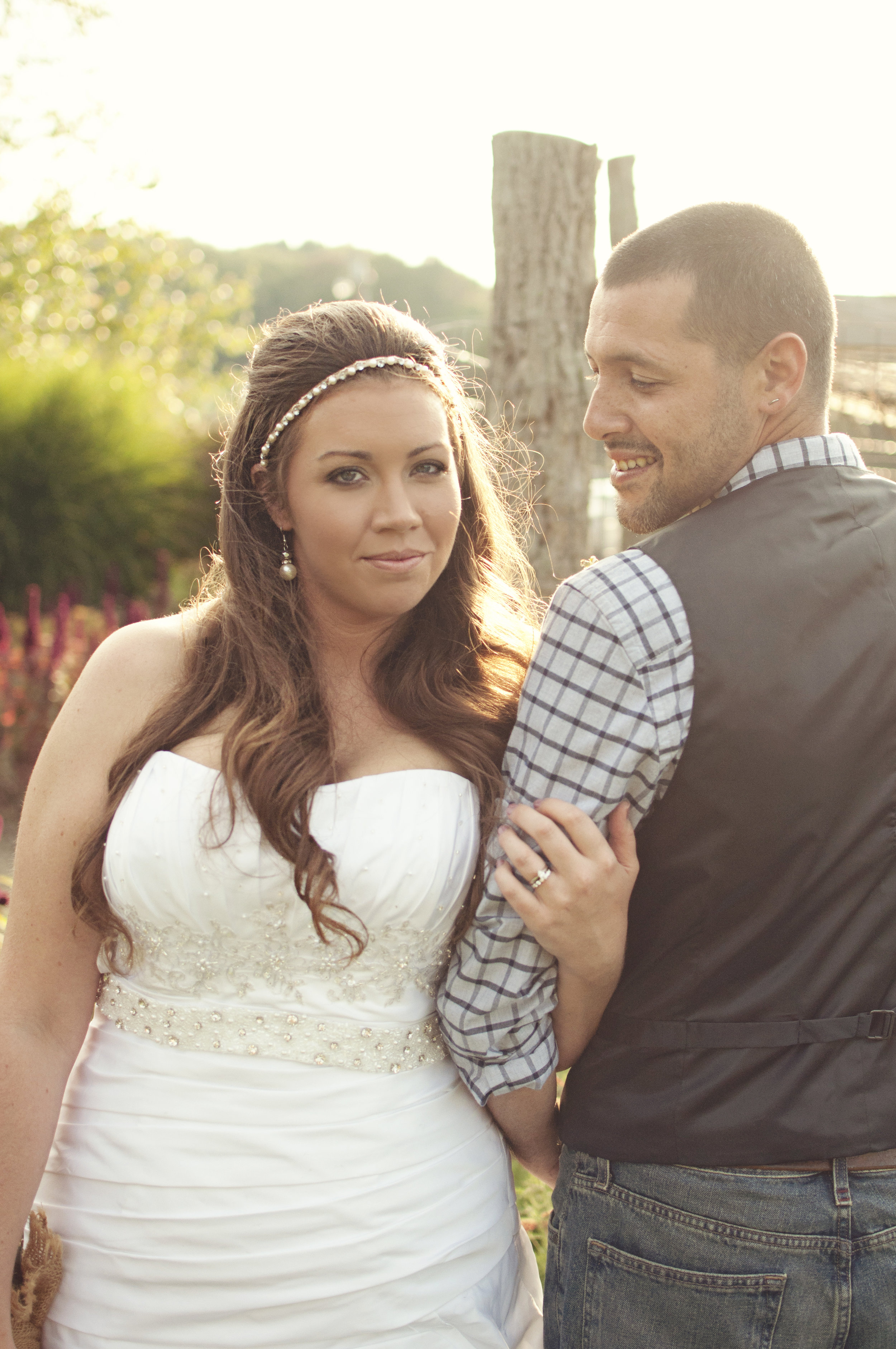 Bride with beaded headband standing with groom looking over shoulder