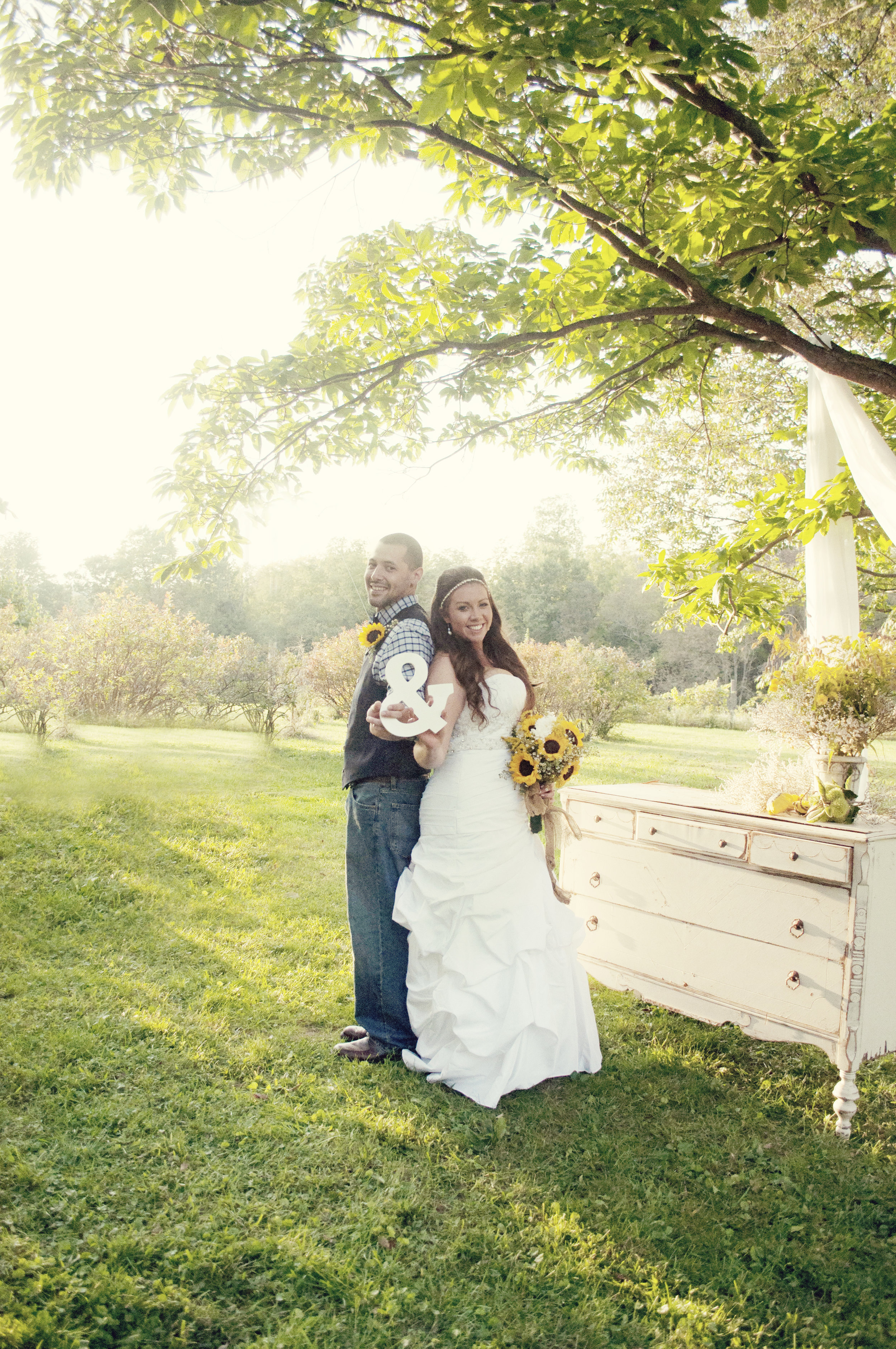 light and airy photo of bride and groom in a field holding ampersand prop