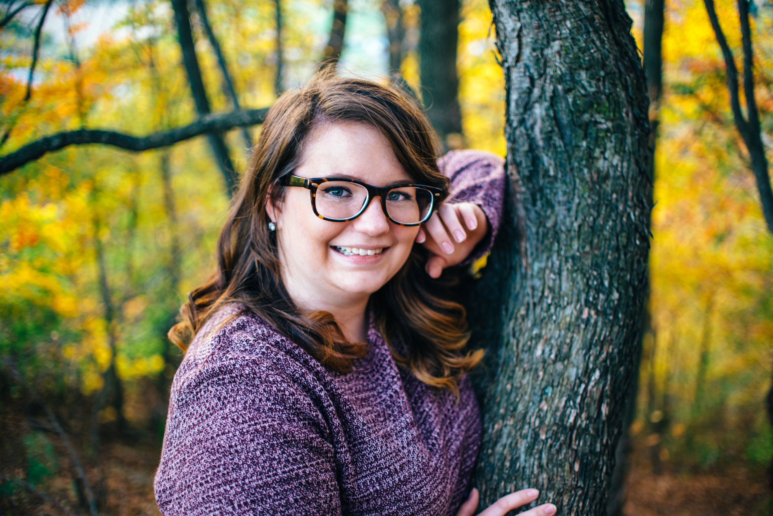 high school senior photo of girl with glasses leaning against a tree in the fall at Chimney Rocks in Hollidaysburg PA