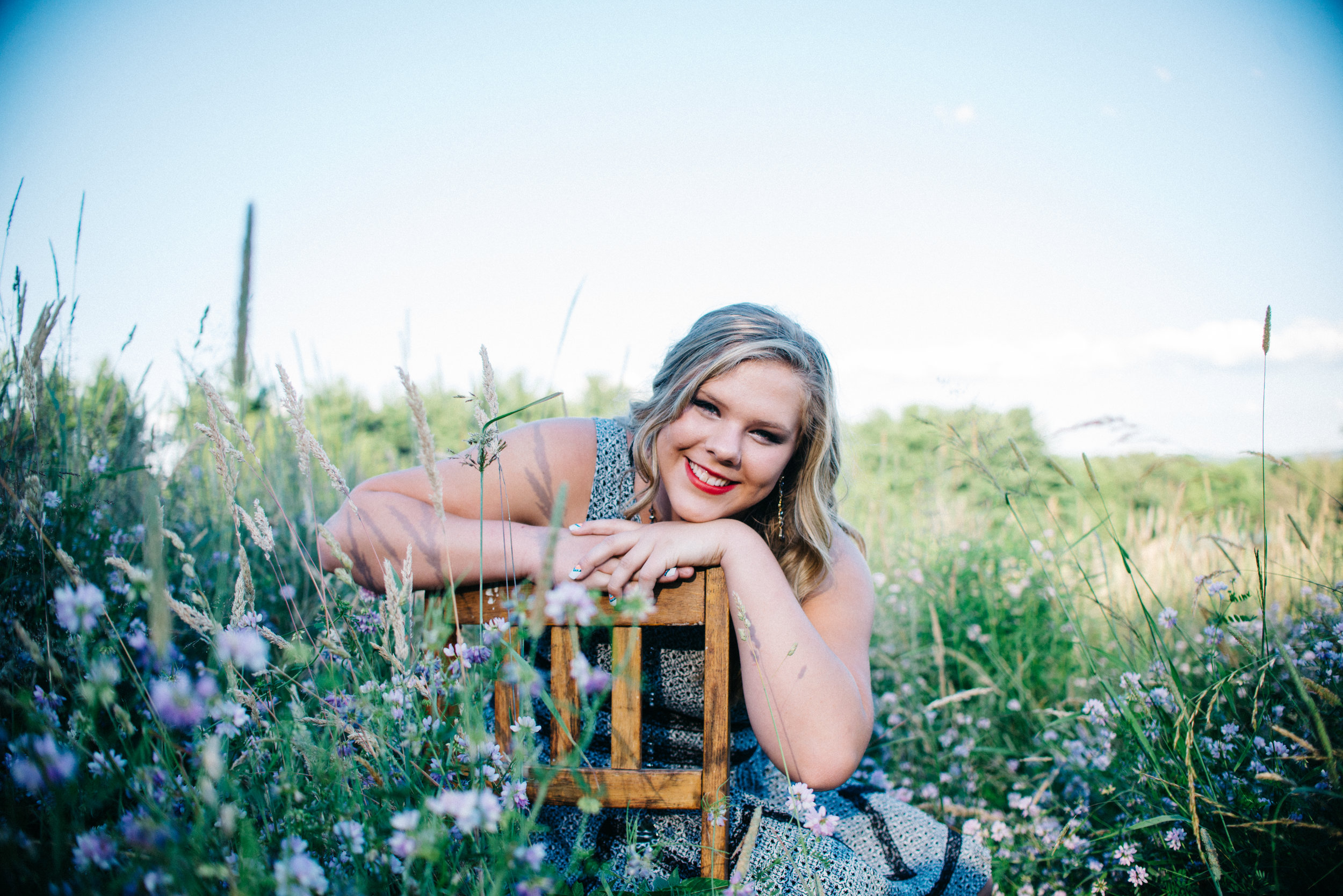High school senior model wearing sundress sitting on wooden chair in a field of flowers