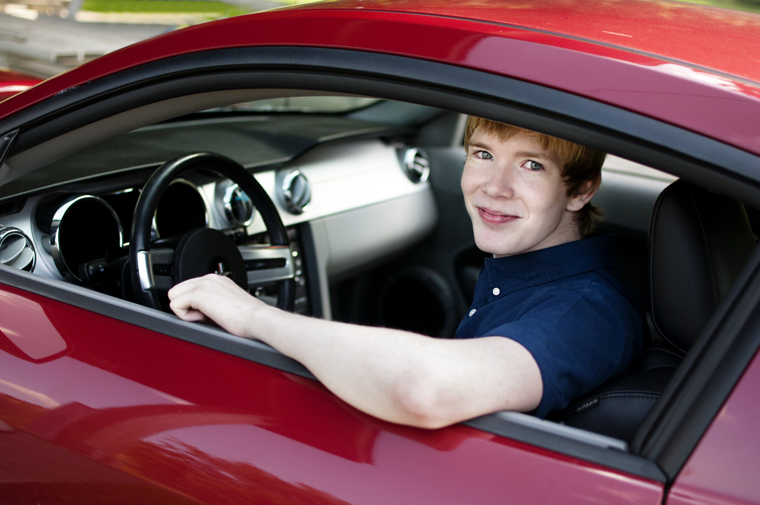 blonde high school senior male model in red ford mustang claifornia special