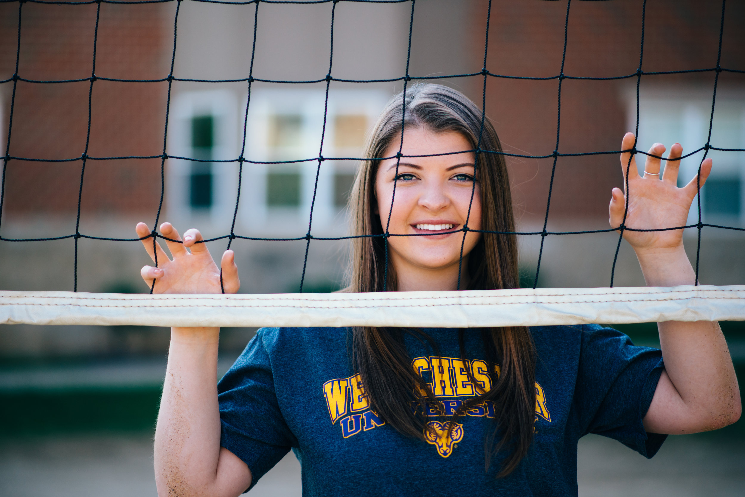 high school senior model behind volleyball net with Westchester University college shirt