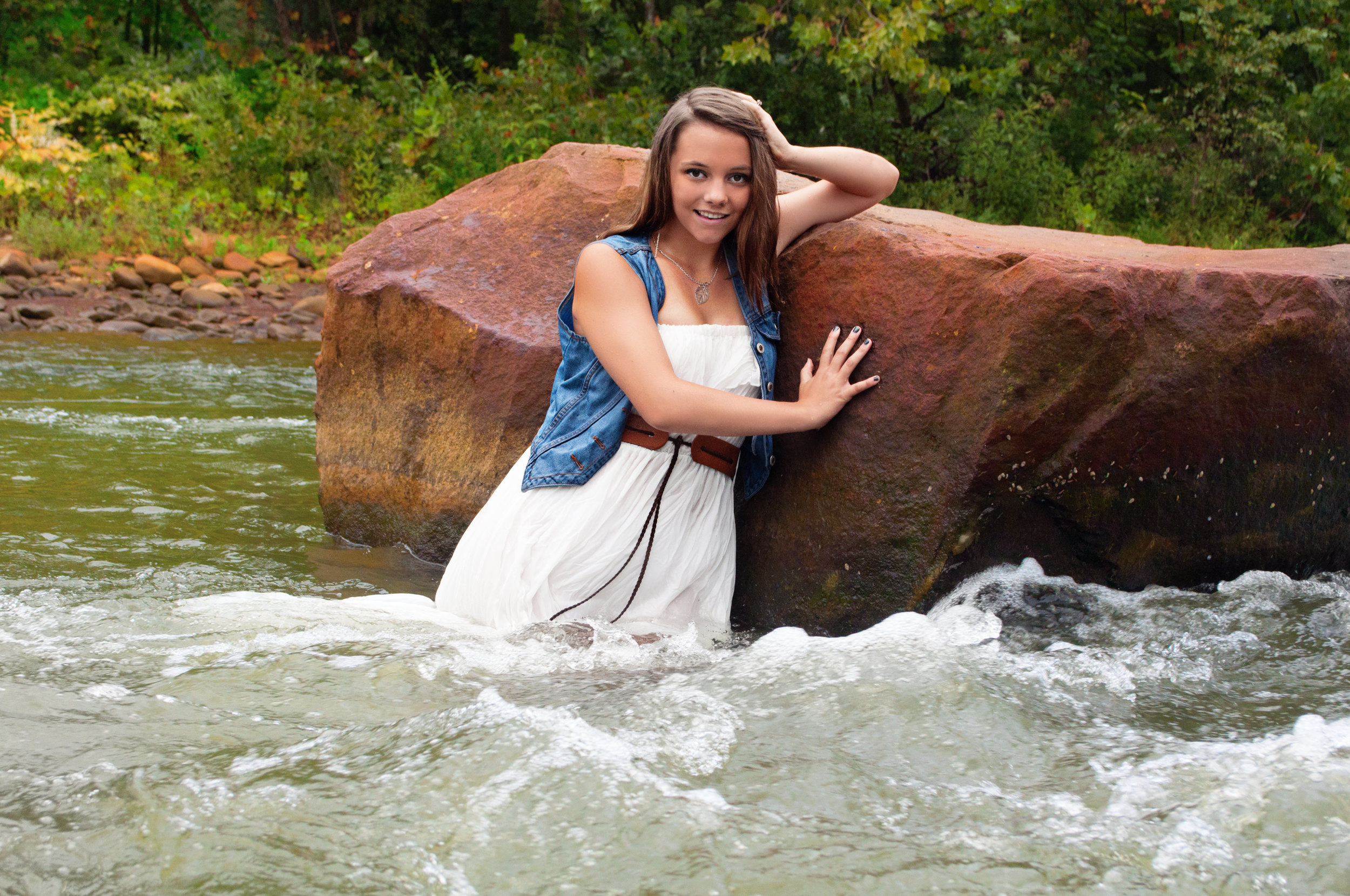 high school senior model standing in water by rocks for senior photos