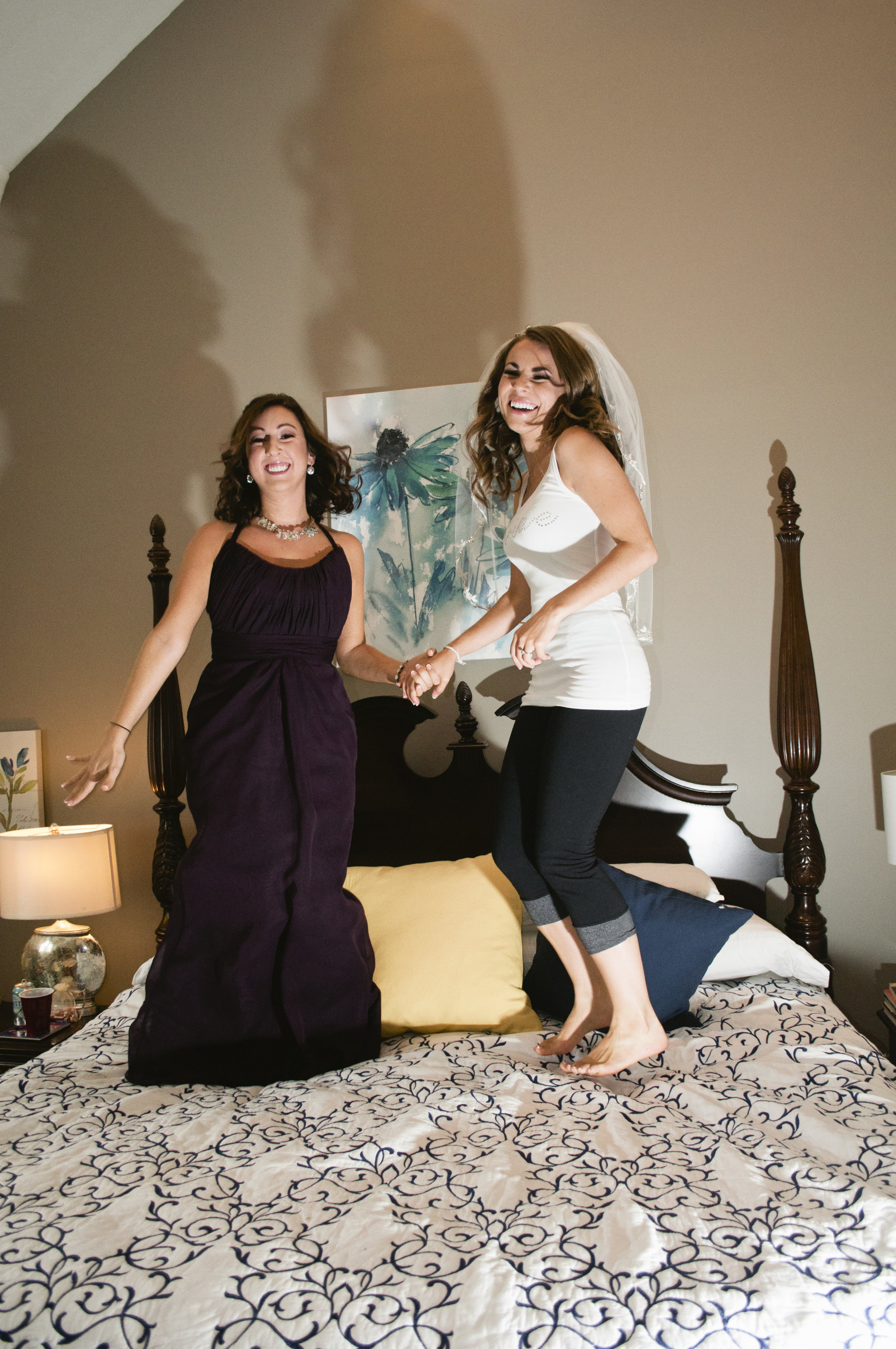 Bride with Maid of Honor jumping on bed the morning of the wedding