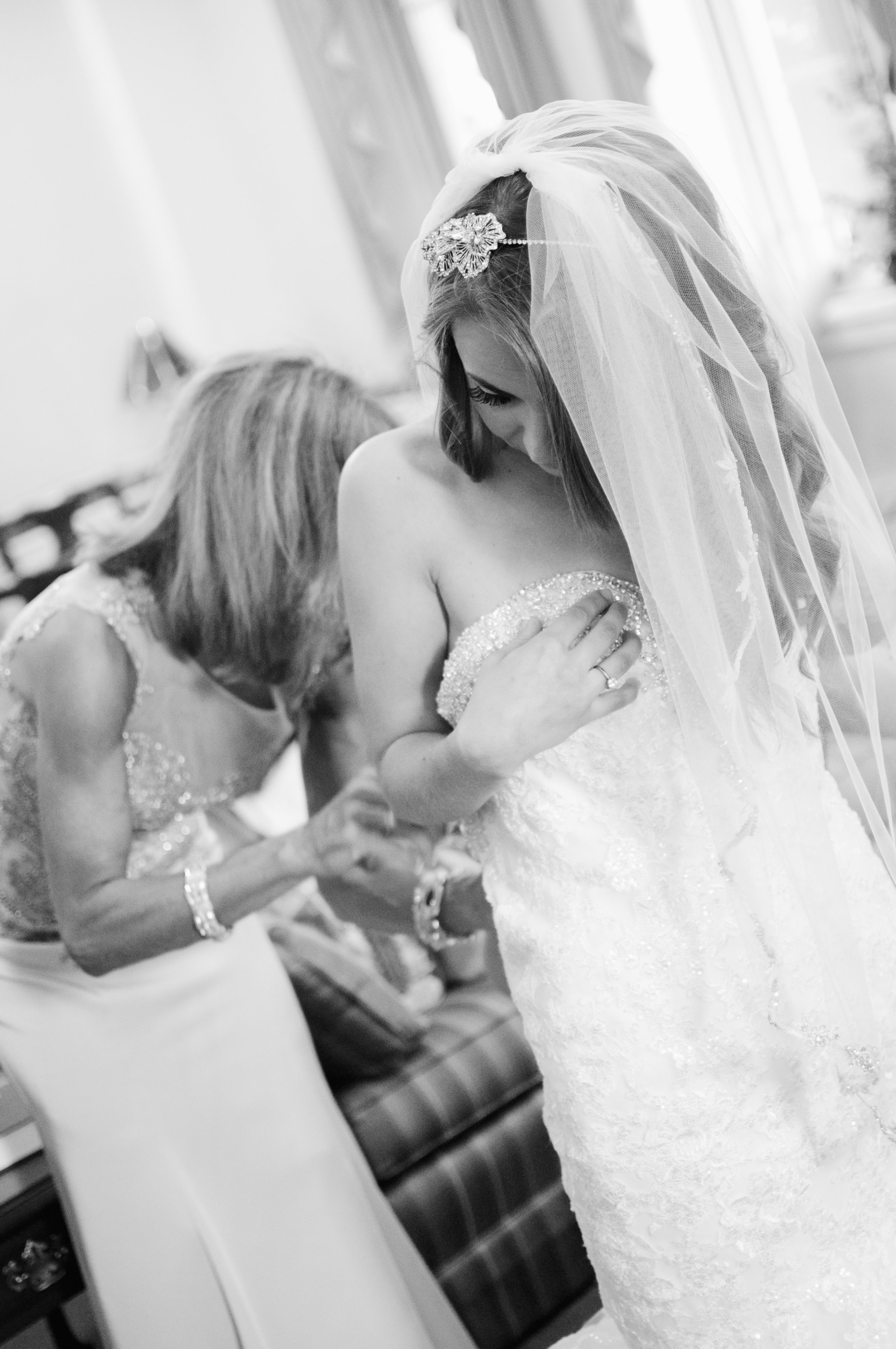 black and white photo of bride with mother upping up gown