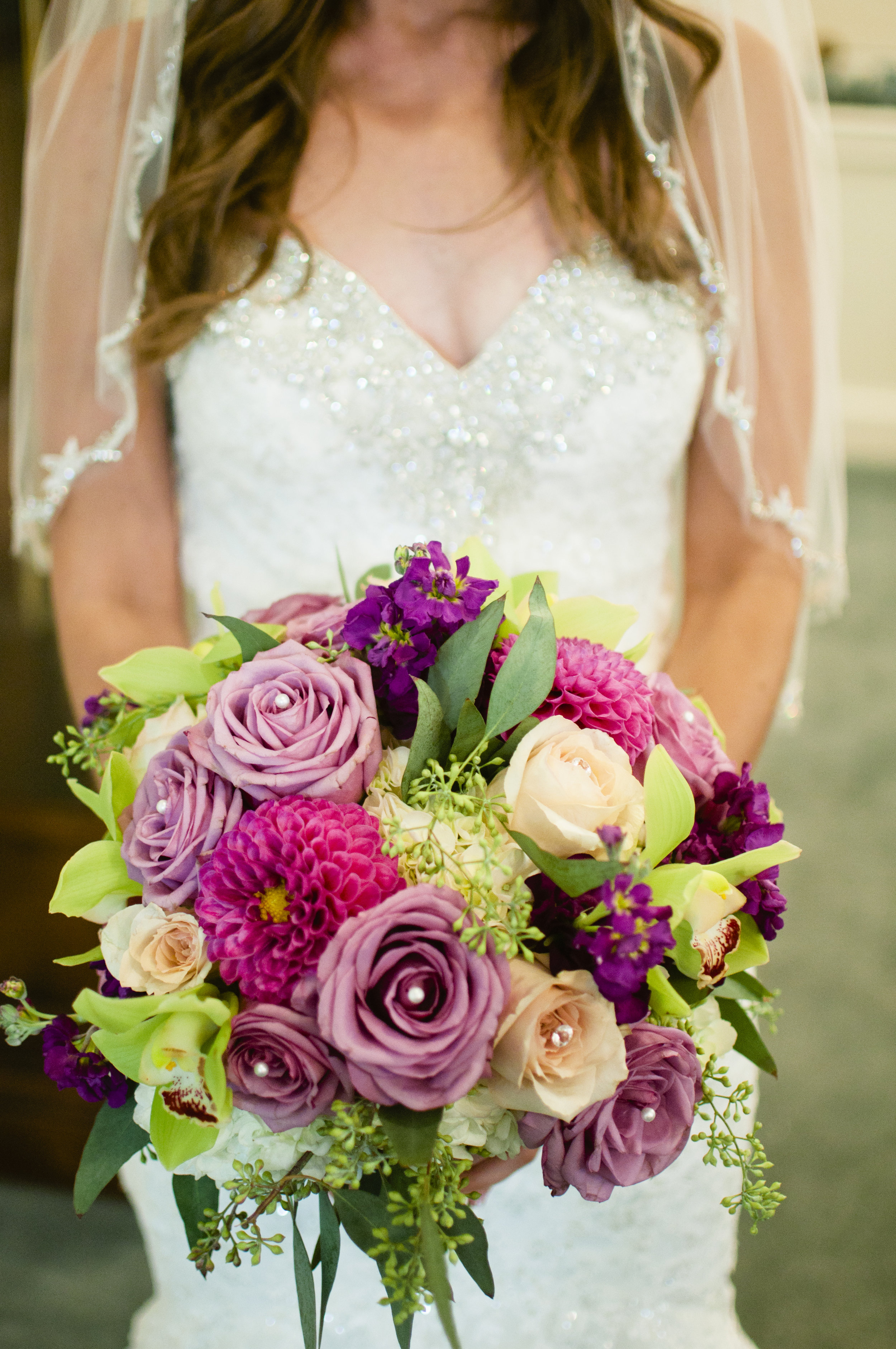 close up of bride holding bouquet with purple zinnias