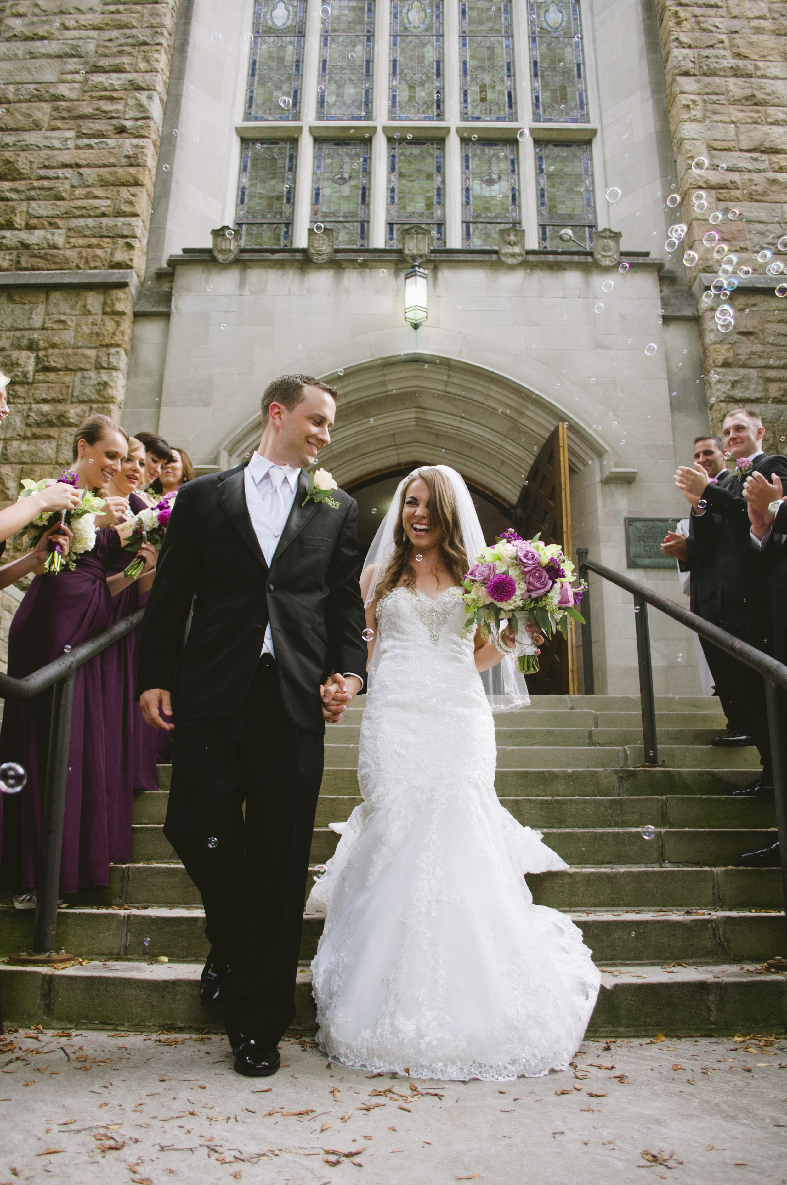bride and groom exiting church with bubbles coming down staircase