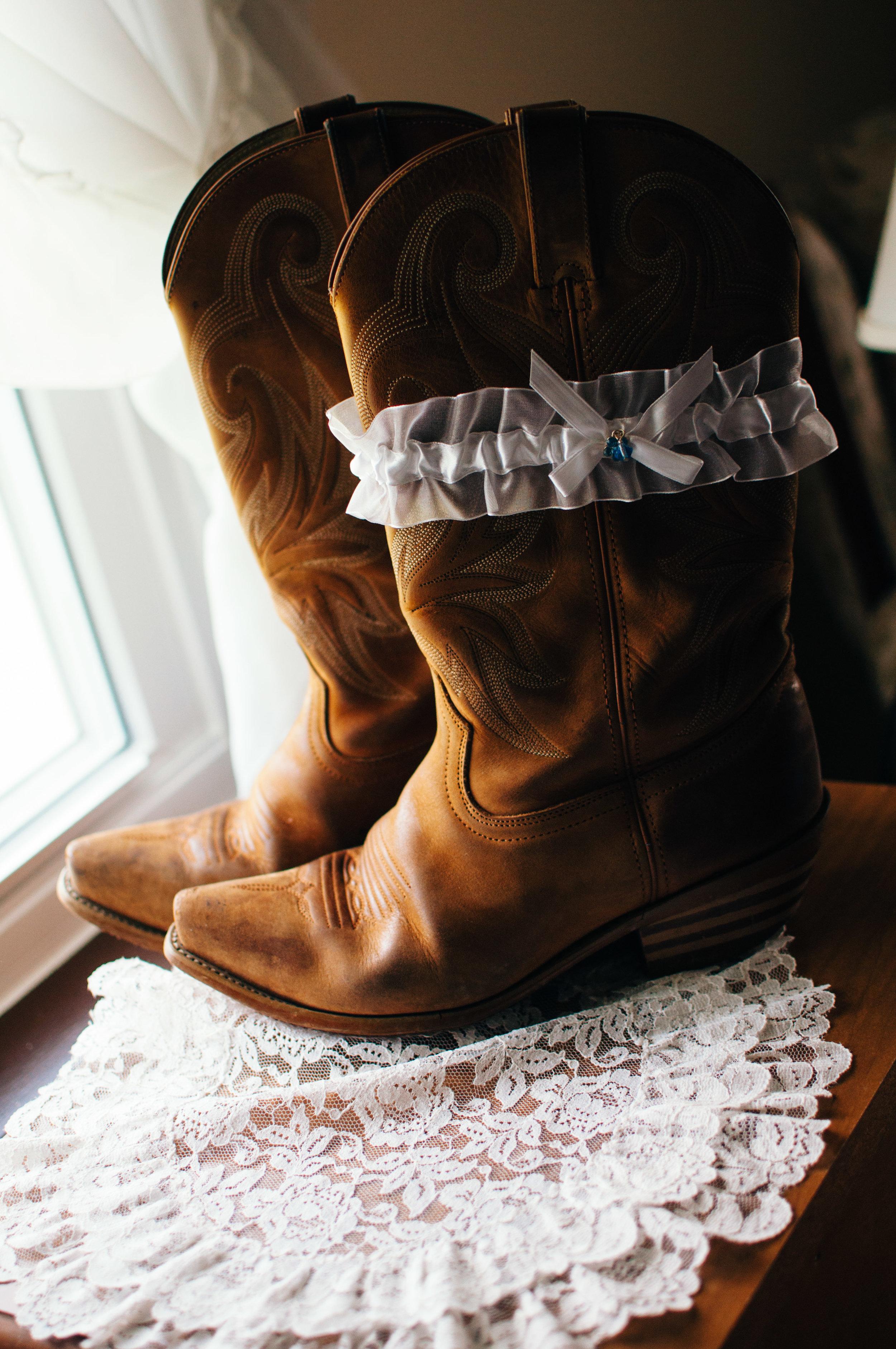 wedding garter with something blue on brides western cowboy boots worn under her wedding dress