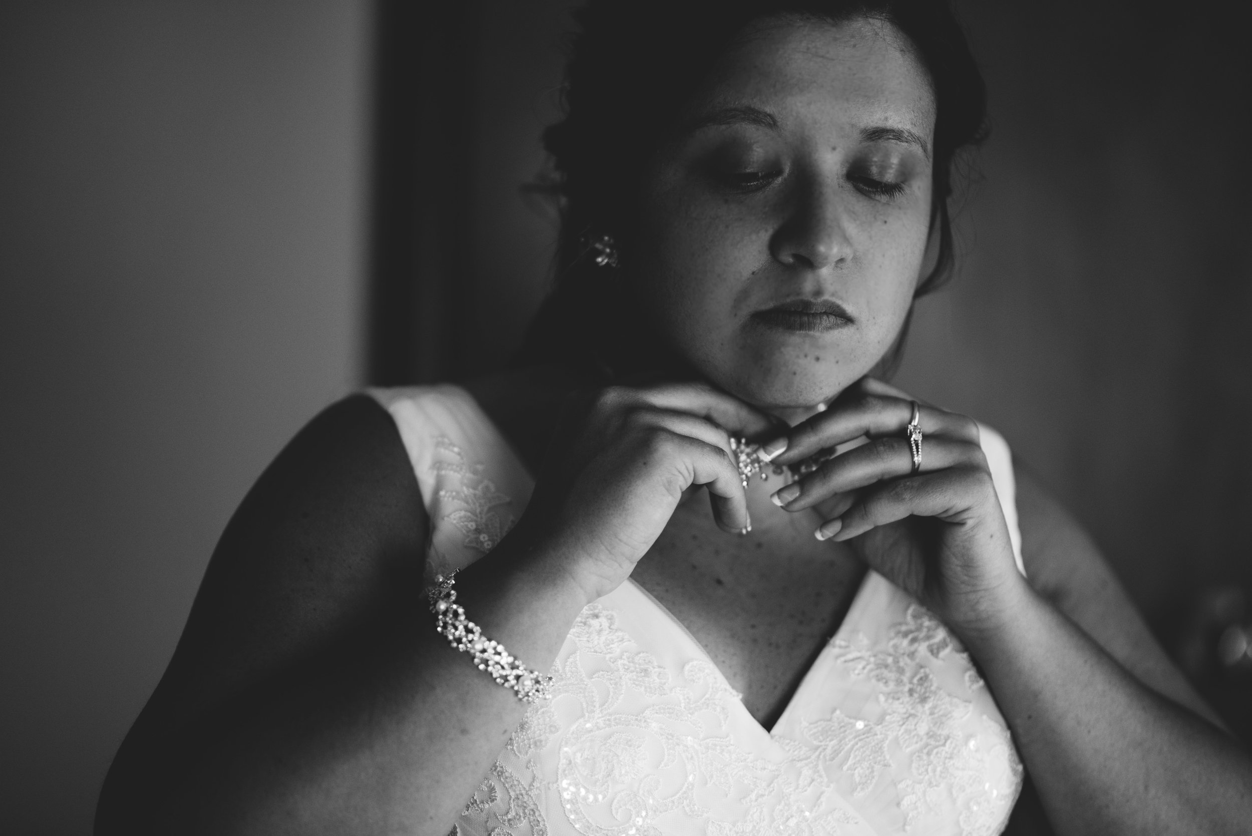 moody black and white candid photo of bride putting necklace on