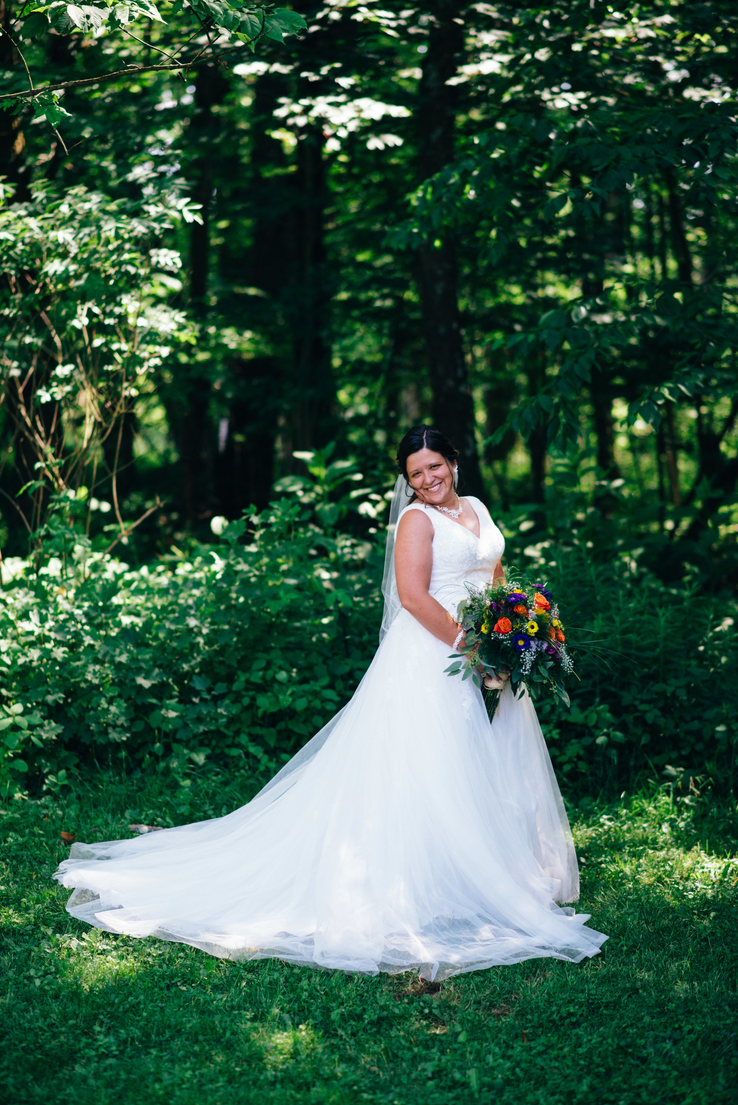 bride with tulle gown and orange and purple bouquet standing on the edge of a forest