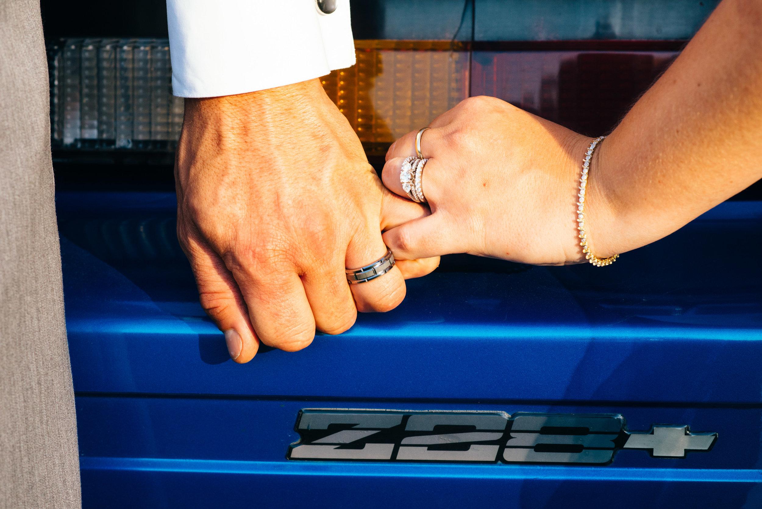 Bride and groom pinky swear near grooms roayl blue z28 classic camaro