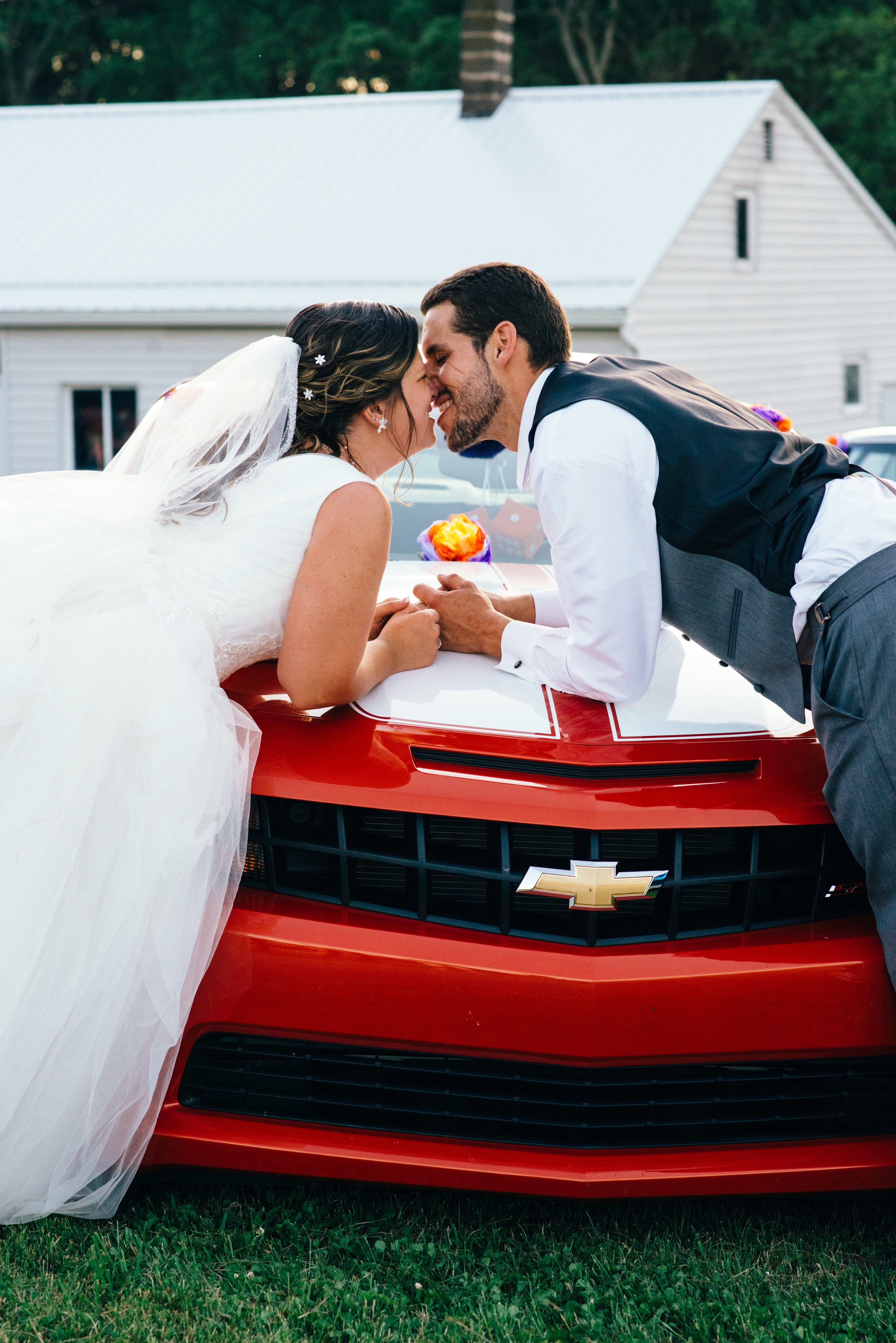 Bride and groom lean across the hood of a new orange chevy camaro for a kiss