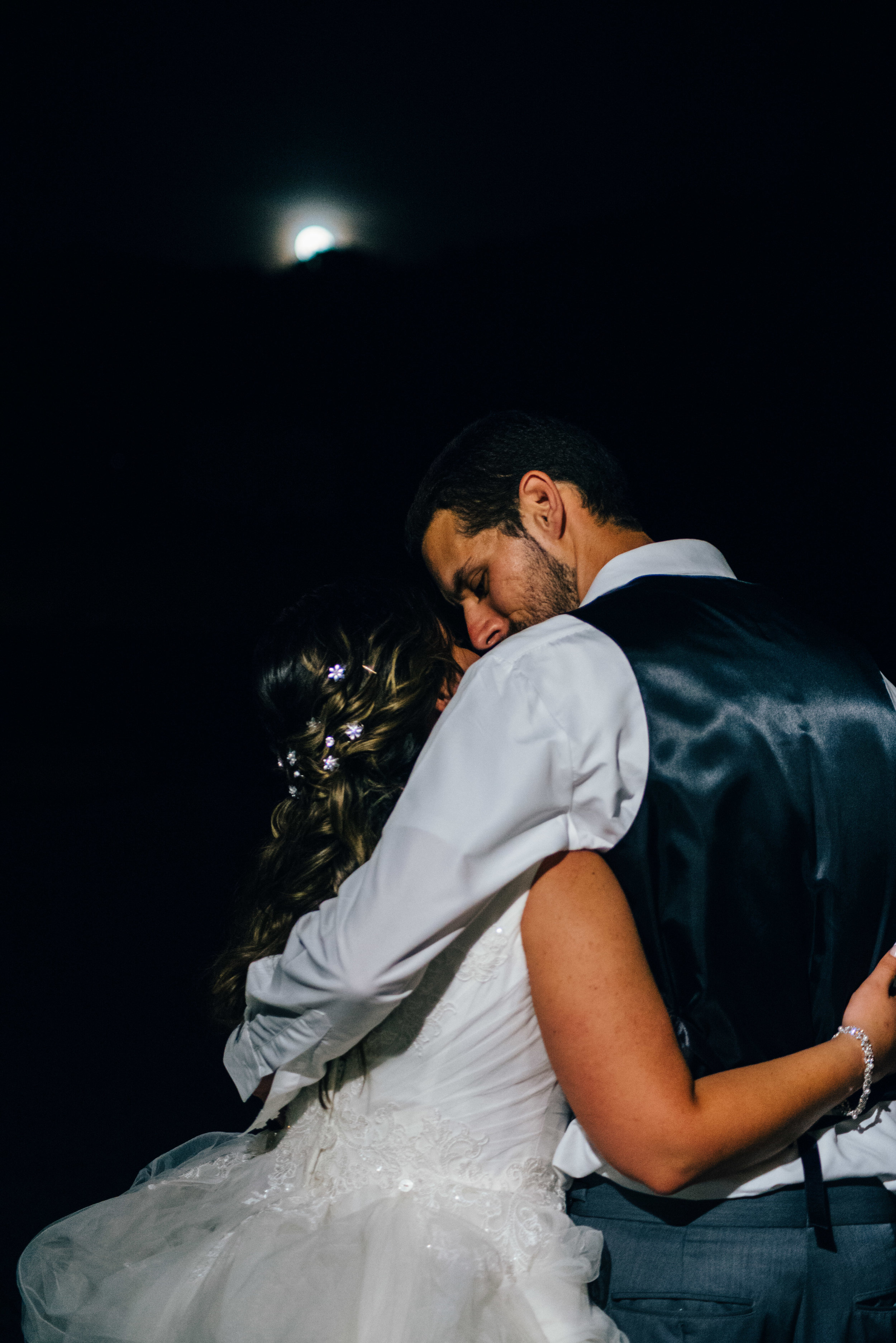 Bride and groom hug from behind under a harvest moon at The Farm on the Ridge in Hooversville PA