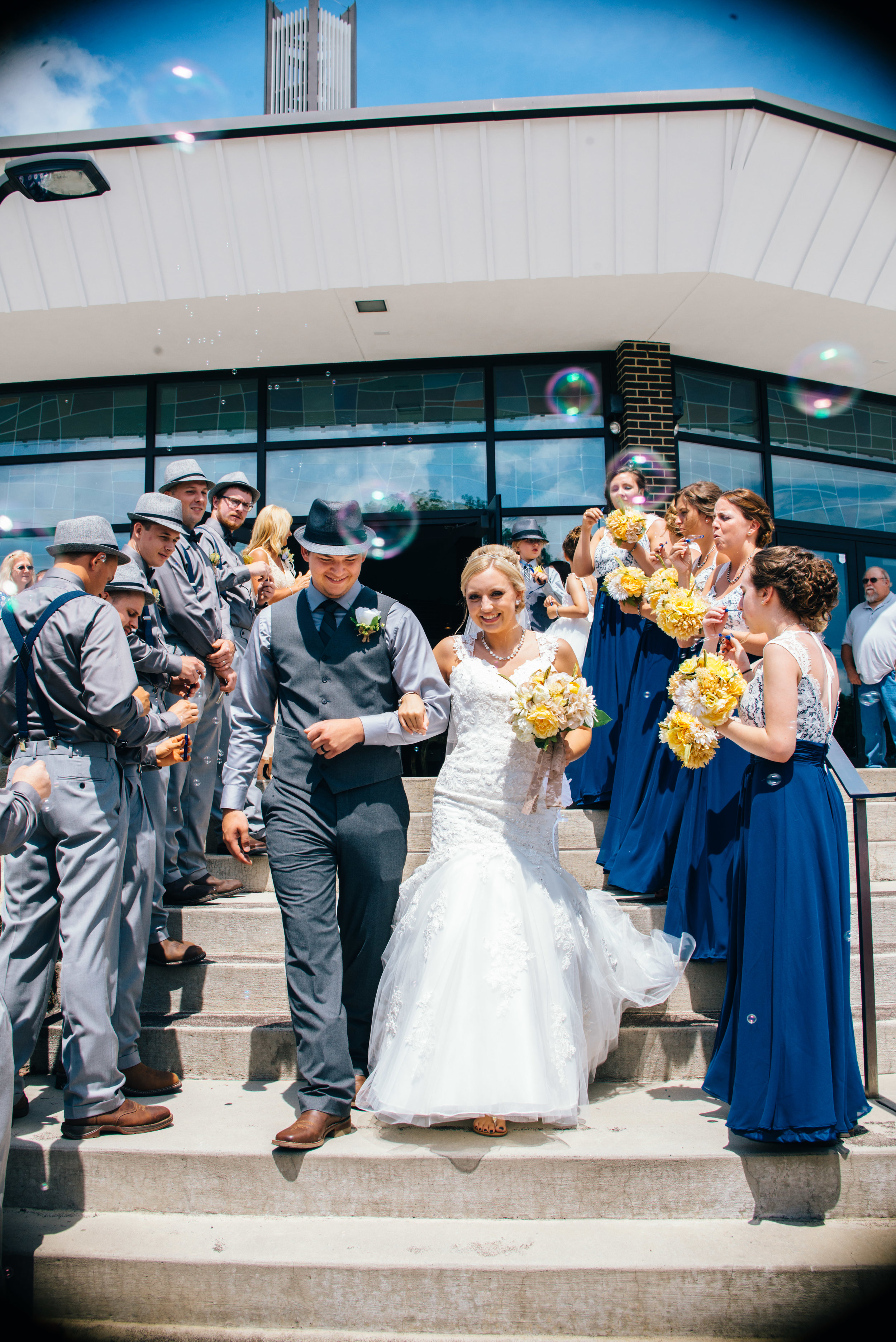 Bride and groom walking down steps outside of Ebensburg PA church as guests blow bubbles